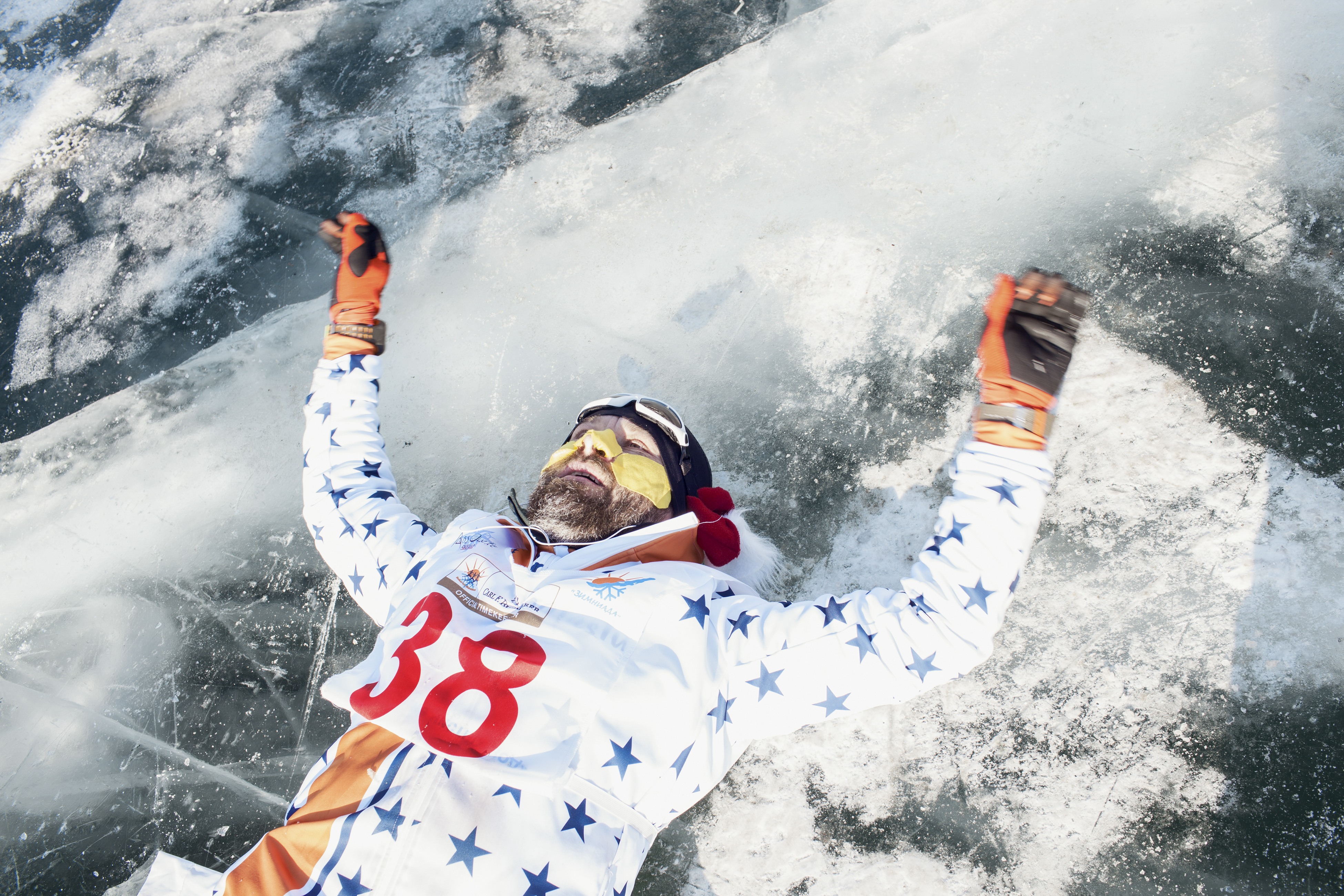 Oskar Szkudlo, a runner from Poland, lies down on the frozen surface of Lake Baikal after finishing the ice marathon on March 2, 2019.