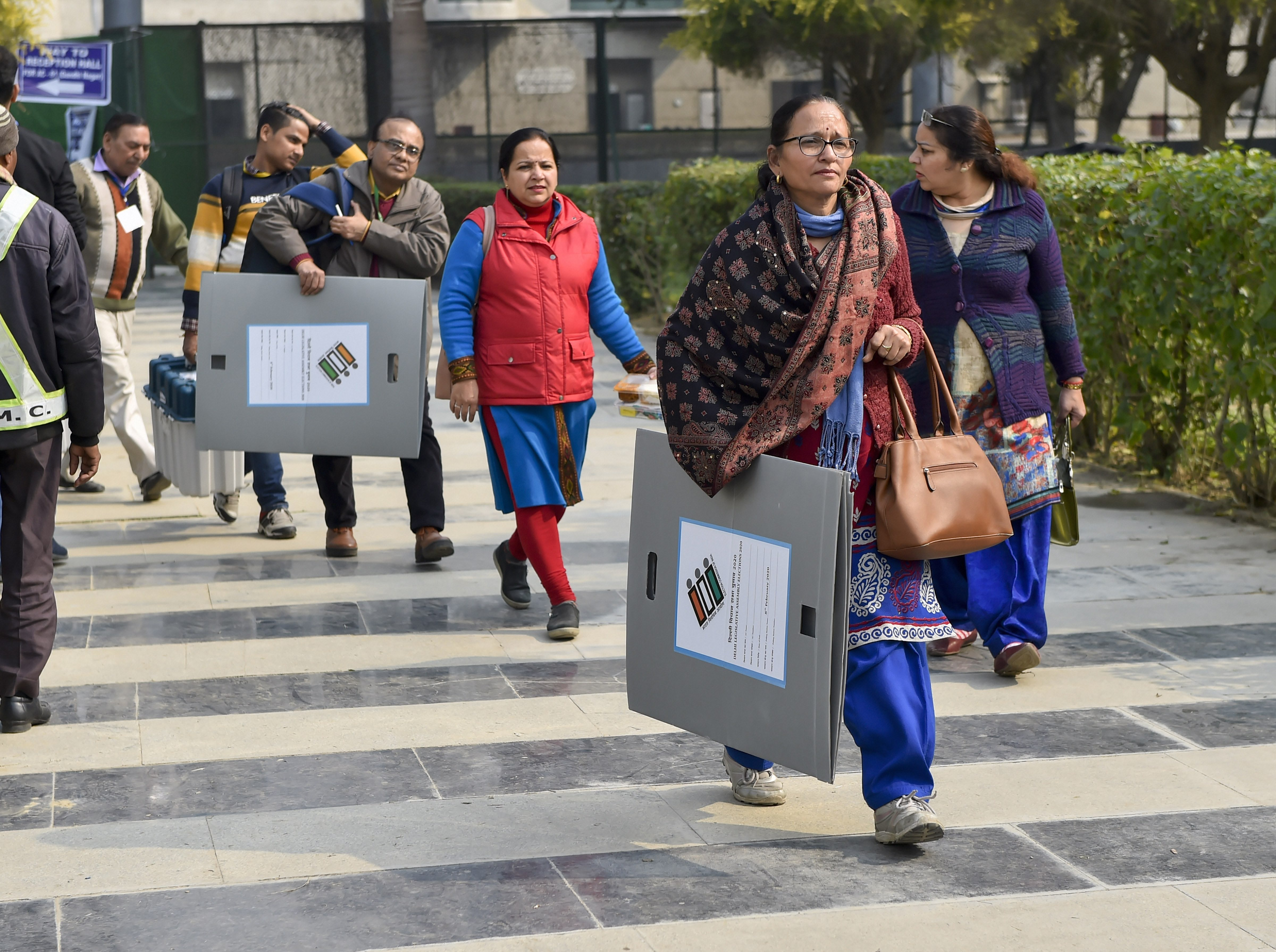 Polling officers carry EVM machines and other polling material as they leave for their polling stations on the eve of the Delhi Assembly elections at Akshardham in New Delhi, Friday, February 7, 2020