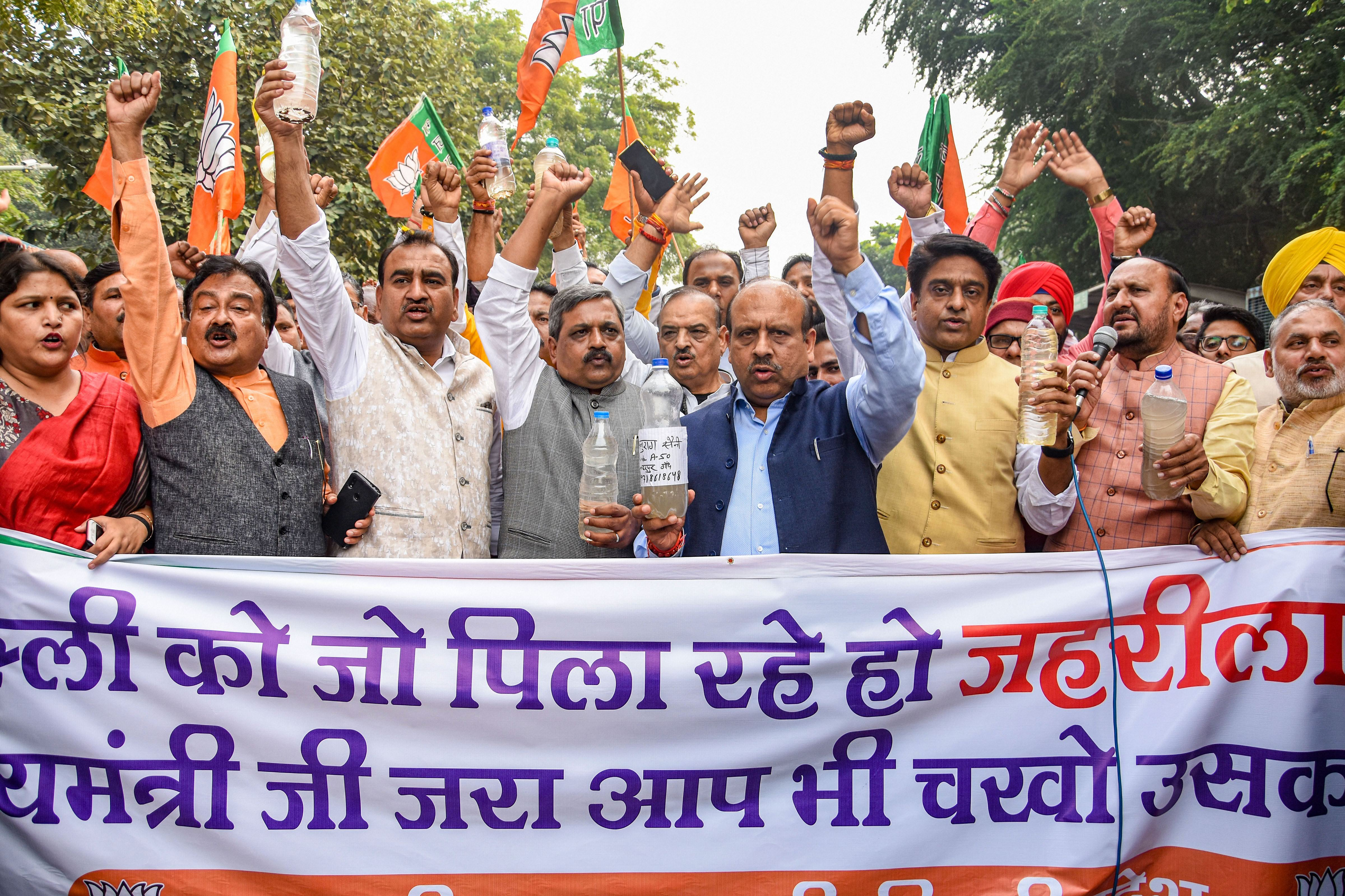 BJP Delhi leaders and supporters, led by city unit chief Manoj Tiwari (unseen), carry water samples from various parts of Delhi as they stage a protest near chief minister Arvind Kejriwal's residence, in New Delhi, Thursday, November 21, 2019.