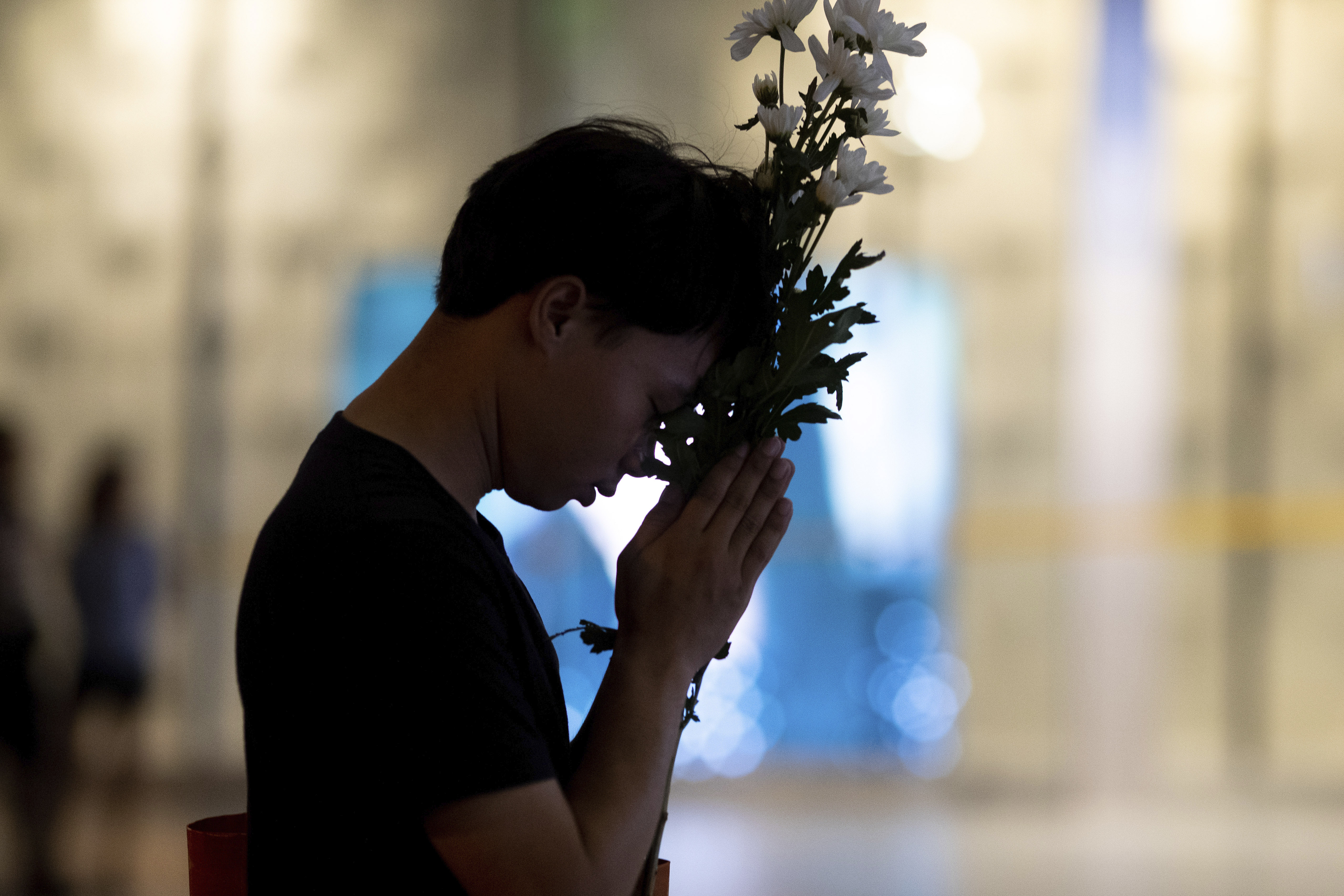 People hold his bouquet during a memorial service at Terminal 21 Korat mall in Nakhon Ratchasima, Thailand on Sunday