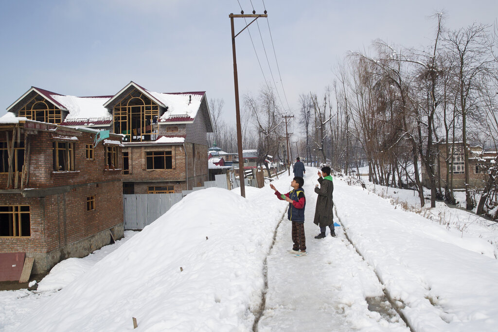 Kashmiri children fly kites on a snow-covered road on the outskirts of Srinagar.