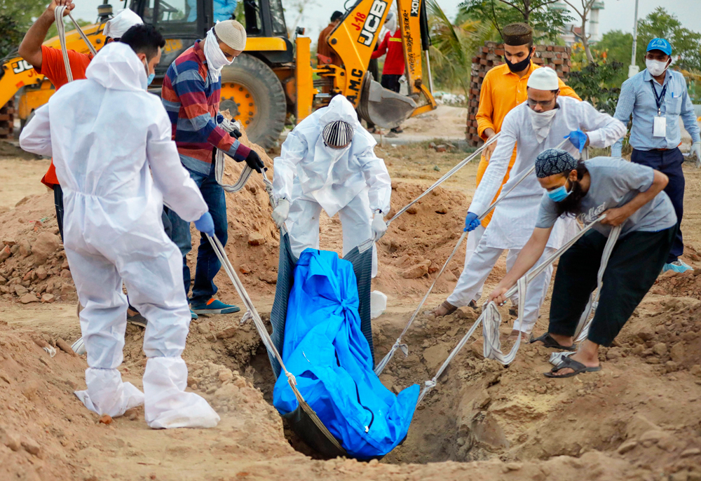 Medics and family members perform burial of a person who died of Covid-19, during the nationwide lockdown, in Ahmedabad, Thursday, April 30, 2020.