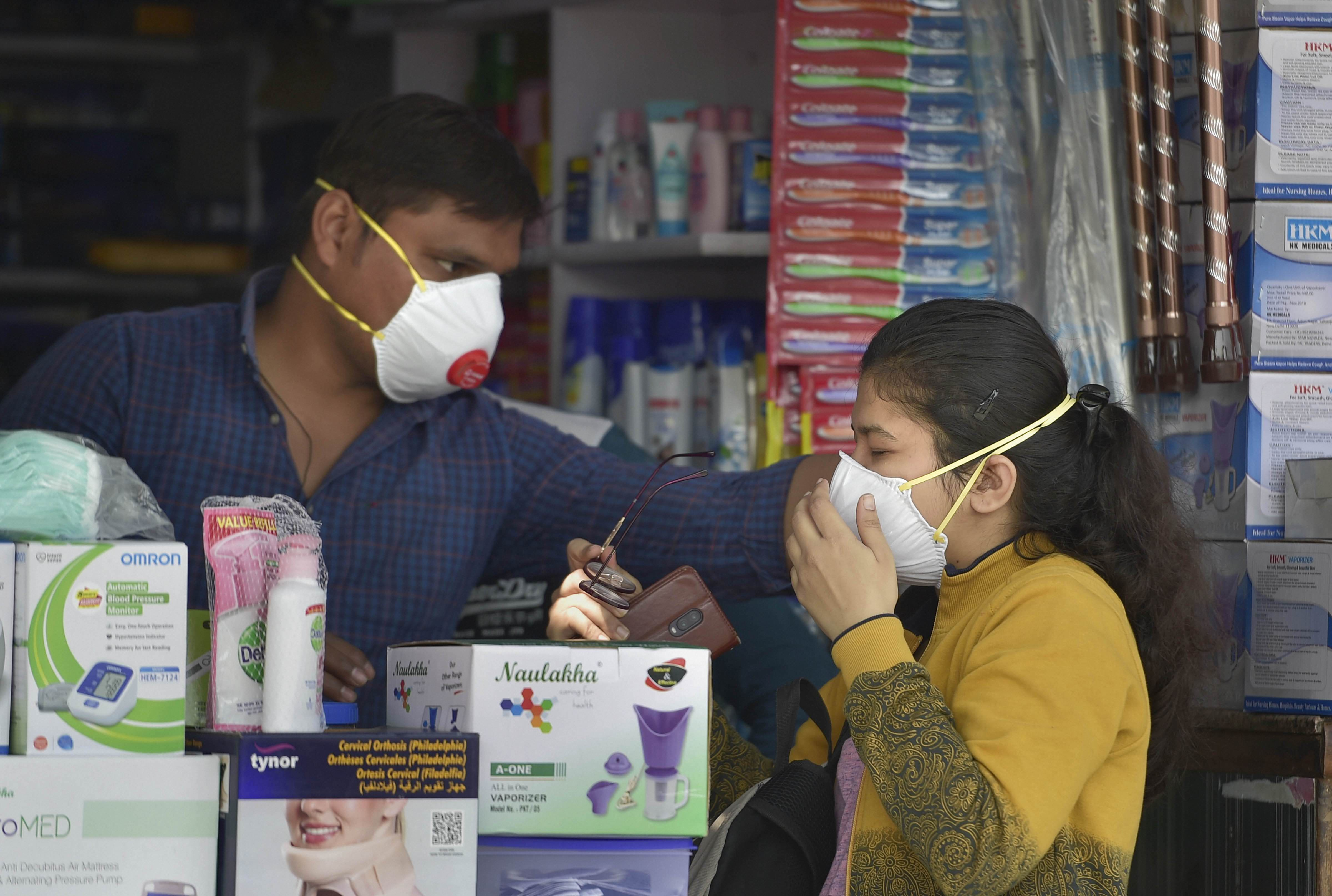 A salesmen at a chemist shop helps a buyer wear her protective mask, in wake of novel coronavirus, outside Safdarjung Hospital, in New Delhi, Wednesday, March 4, 2020