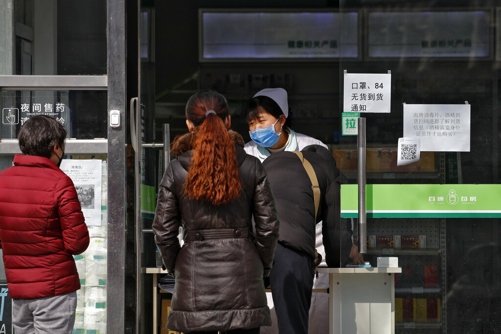 A man fills out personal details for his prescription purchase at a pharmacy during the coronavirus outbreak in Beijing on Sunday