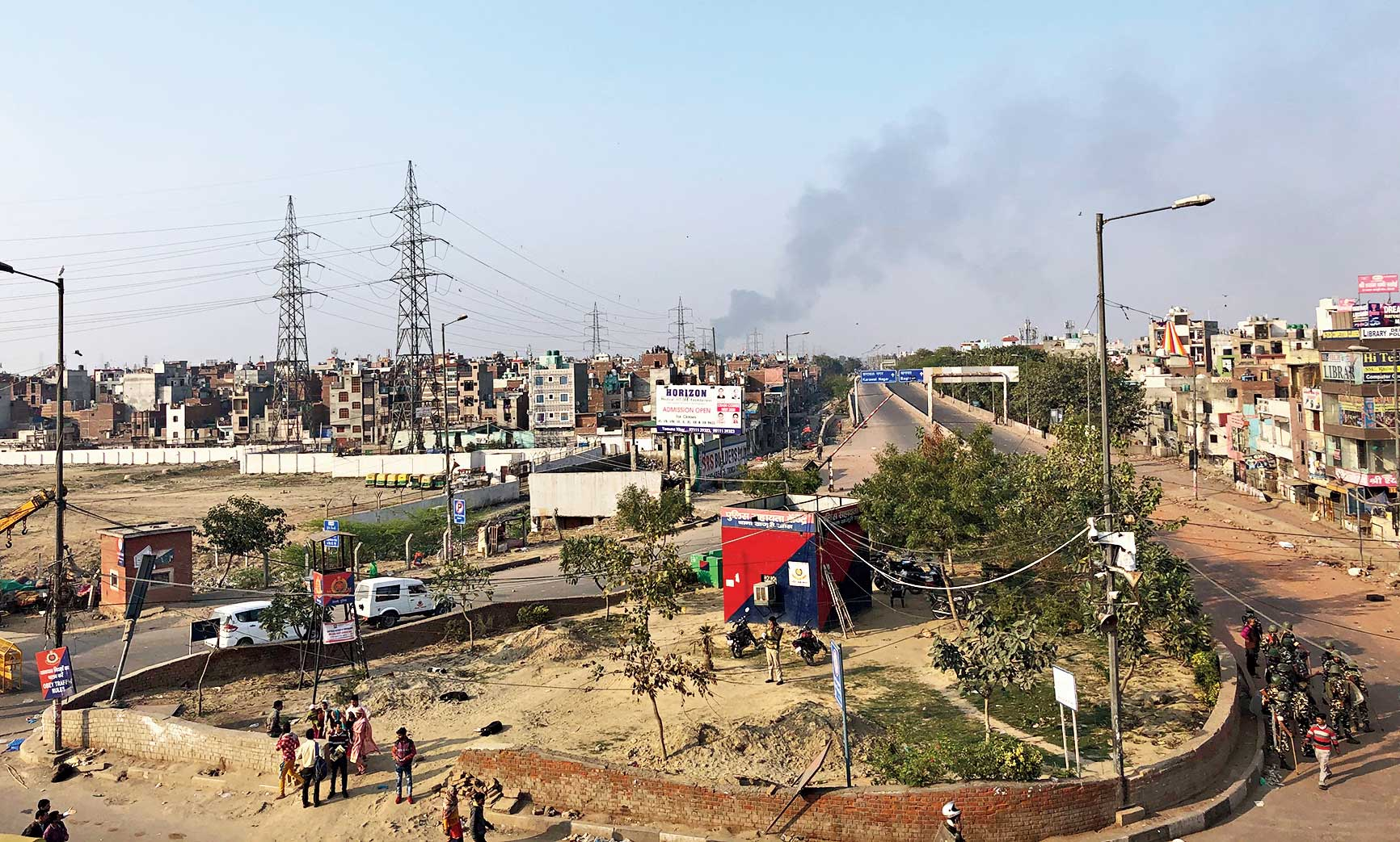 Black smoke rises into the sky after shops are set on fire during the violence in the Bhajanpura area of New Delhi on Tuesday.
