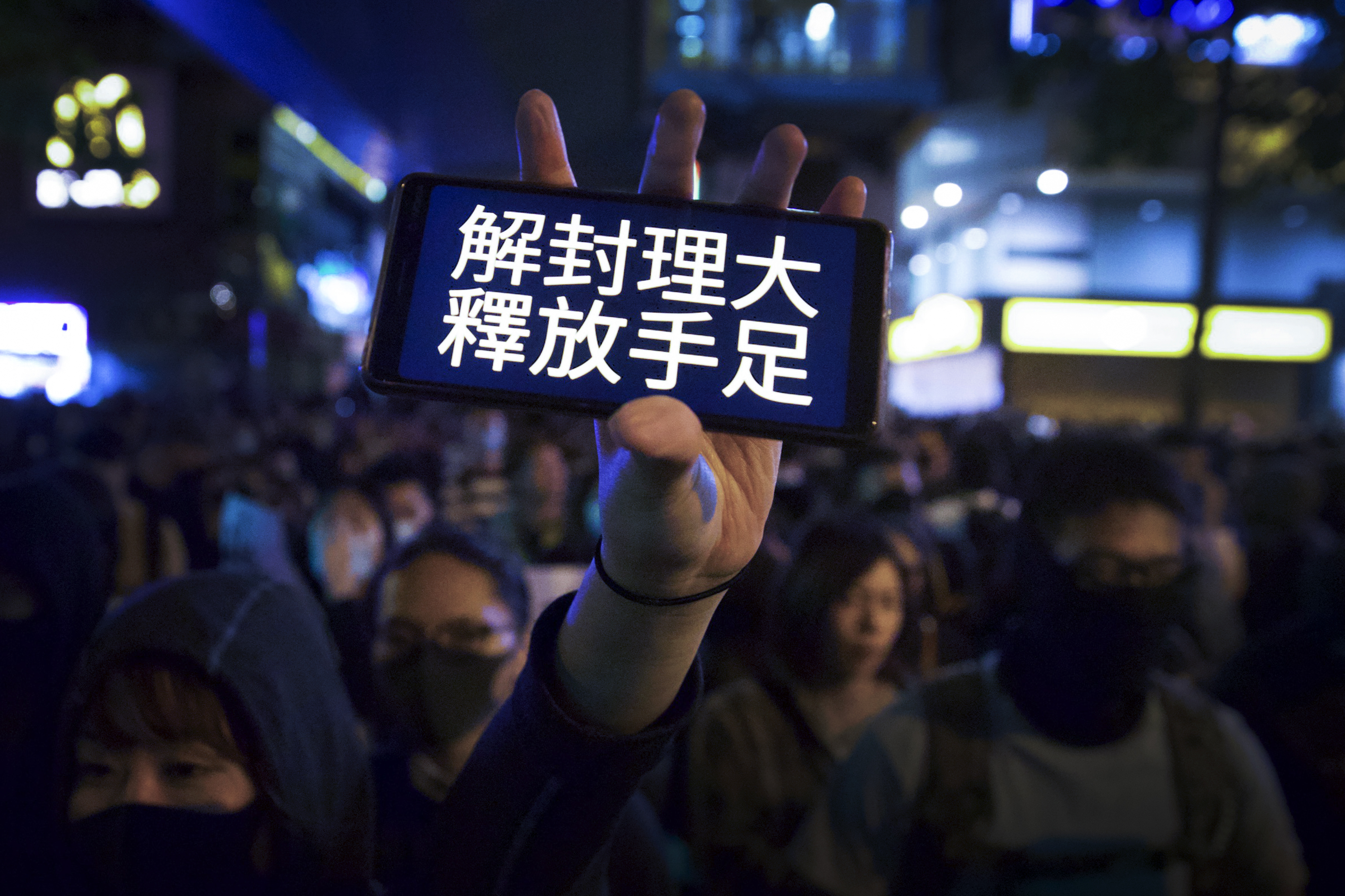 A protester flash her smartphone bearing the words