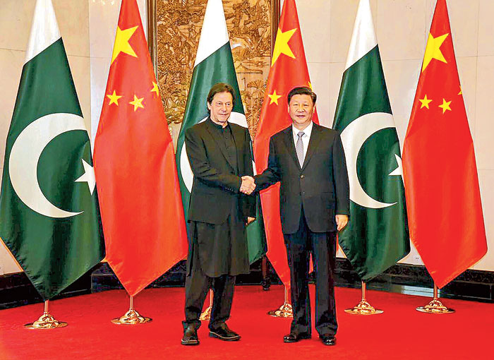 Pakistan Prime Minister Imran Khan and Chinese President Xi Jinping shake hands in Beijing on Wednesday
