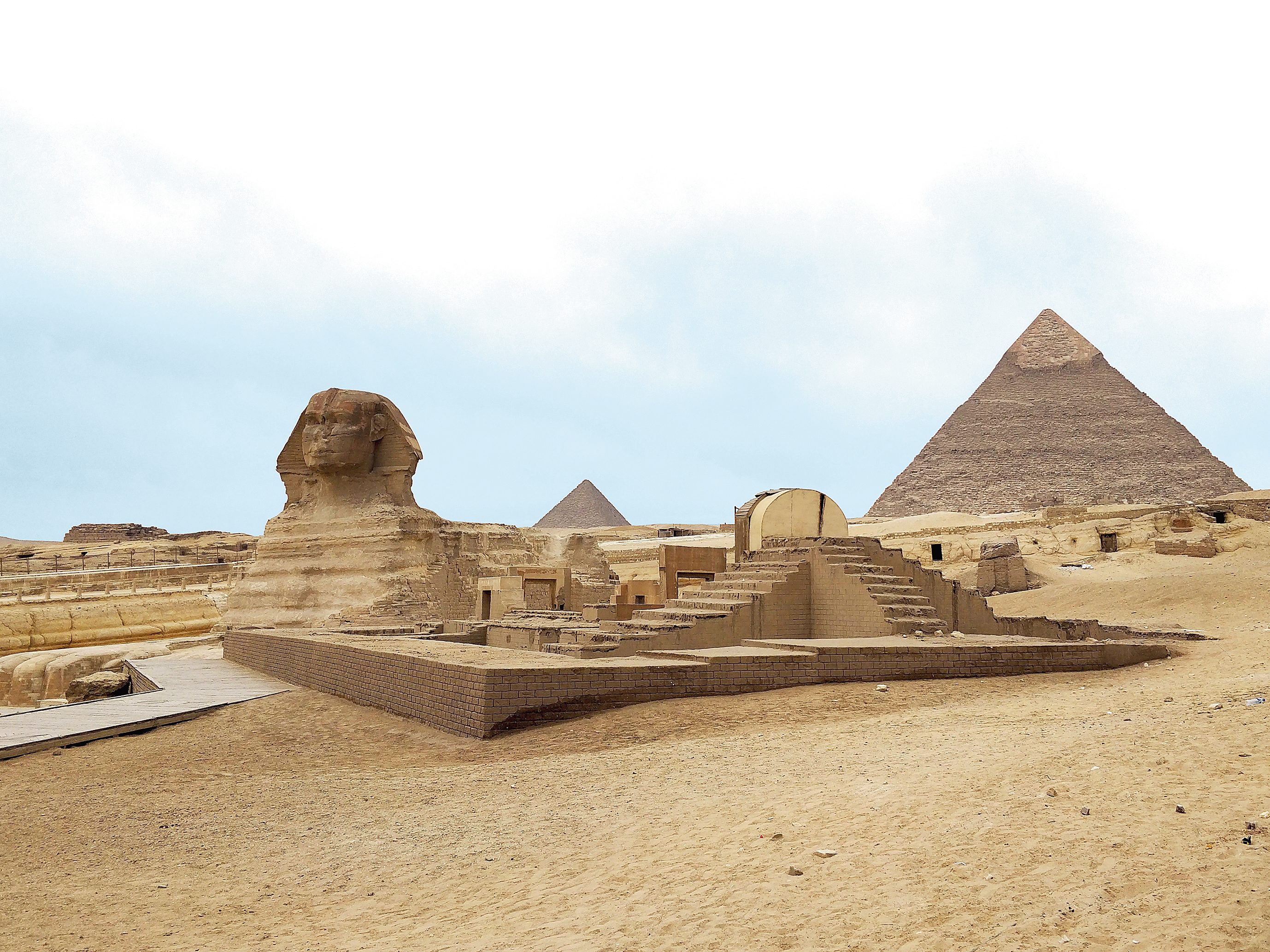 The Sphinx sits proudly in the backdrop of two pyramids at Giza.