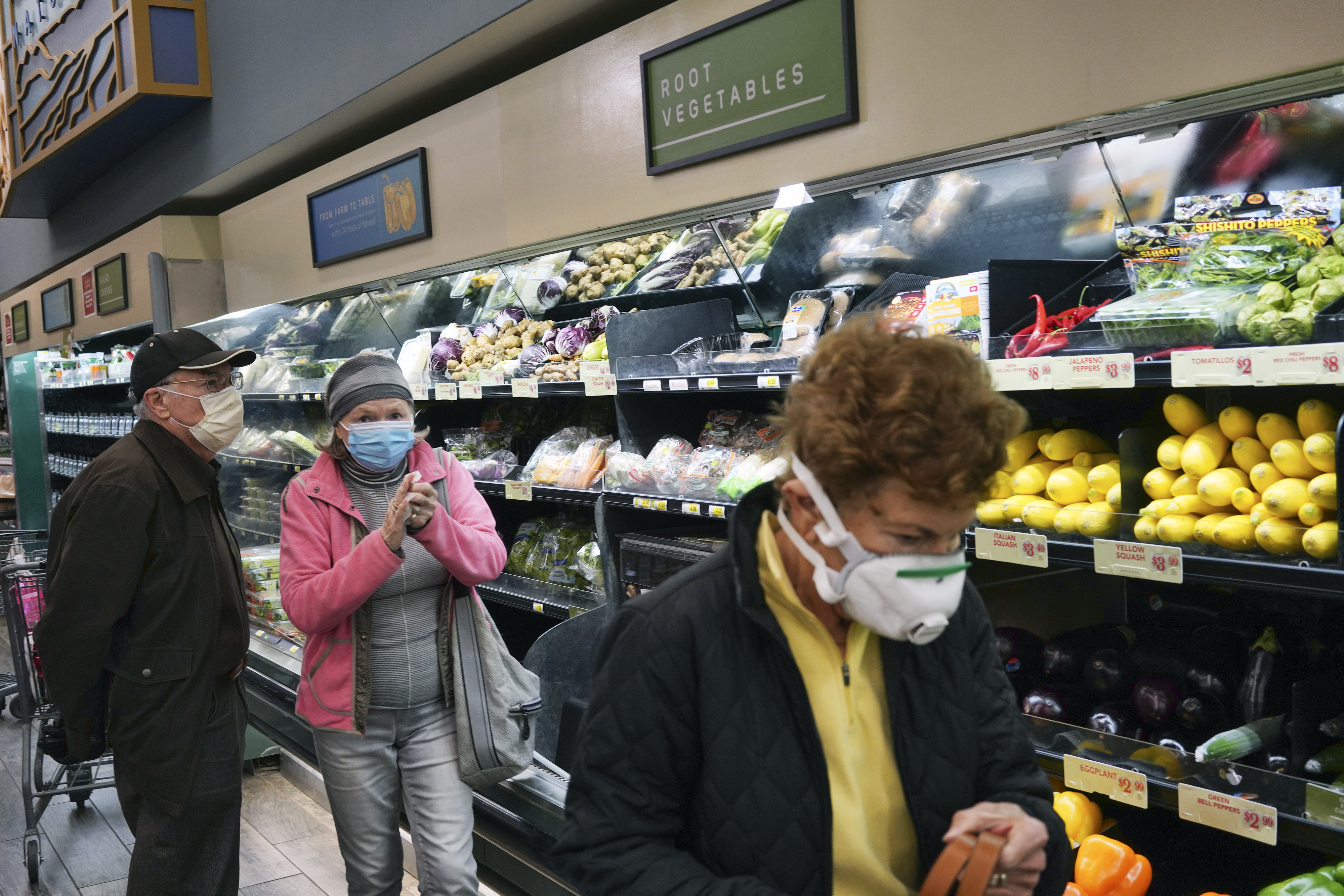 Customers wearing protective masked shop at Gelson's supermarket that opened special morning hours to serve seniors 60-years and older due to coronavirus concerns on Friday
