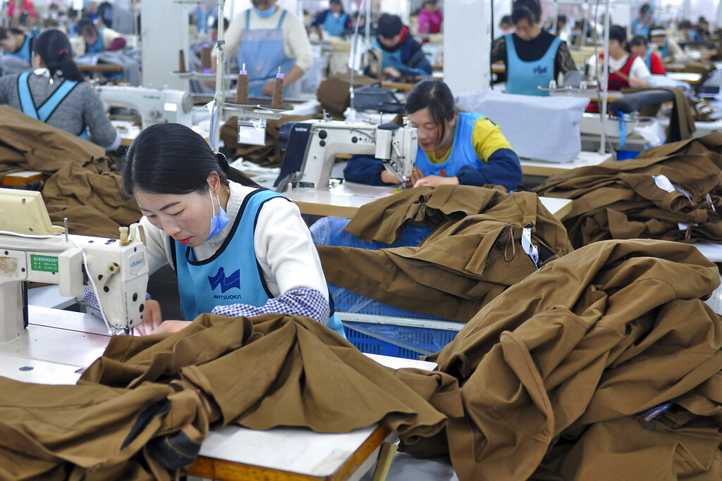 In this Tuesday, April 9, 2019, photo, workers sewing clothing for export at an garment factory in Donghai county in east China's Jiangsu province.