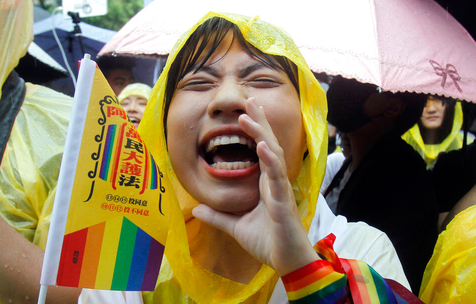 A same-sex marriage supporter cheers outside the Legislative Yuan Friday on May 17, 2019, in Taipei, Taiwan after the legislature passed a law allowing same-sex marriage in a first for Asia.