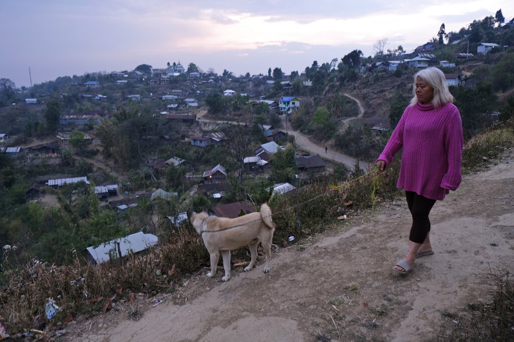 A woman walks her dog, as most people in this mountain village stayed indoors with fears of a rumor of medicine being sprayed from the sky to contain the new virus, in Shangshak village, in the northeastern Indian state of Manipur.