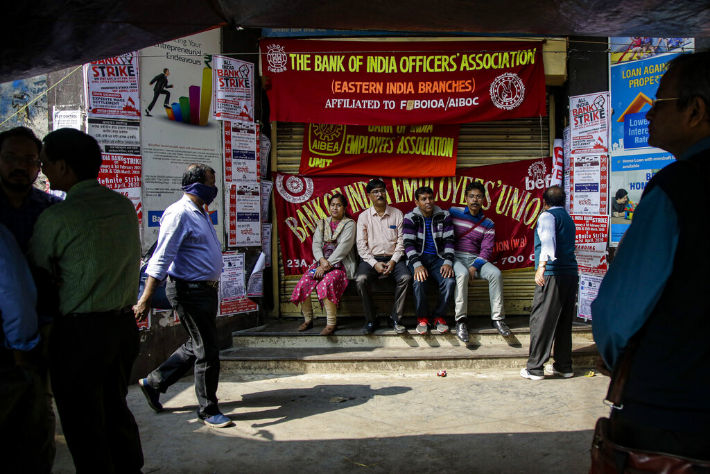 Employees sit in front of a closed bank during a two-day bank strike in Kolkata