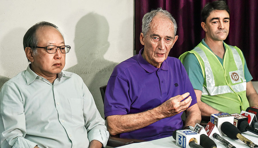 British engineer John Endicott (centre) speaks to the media on Friday.