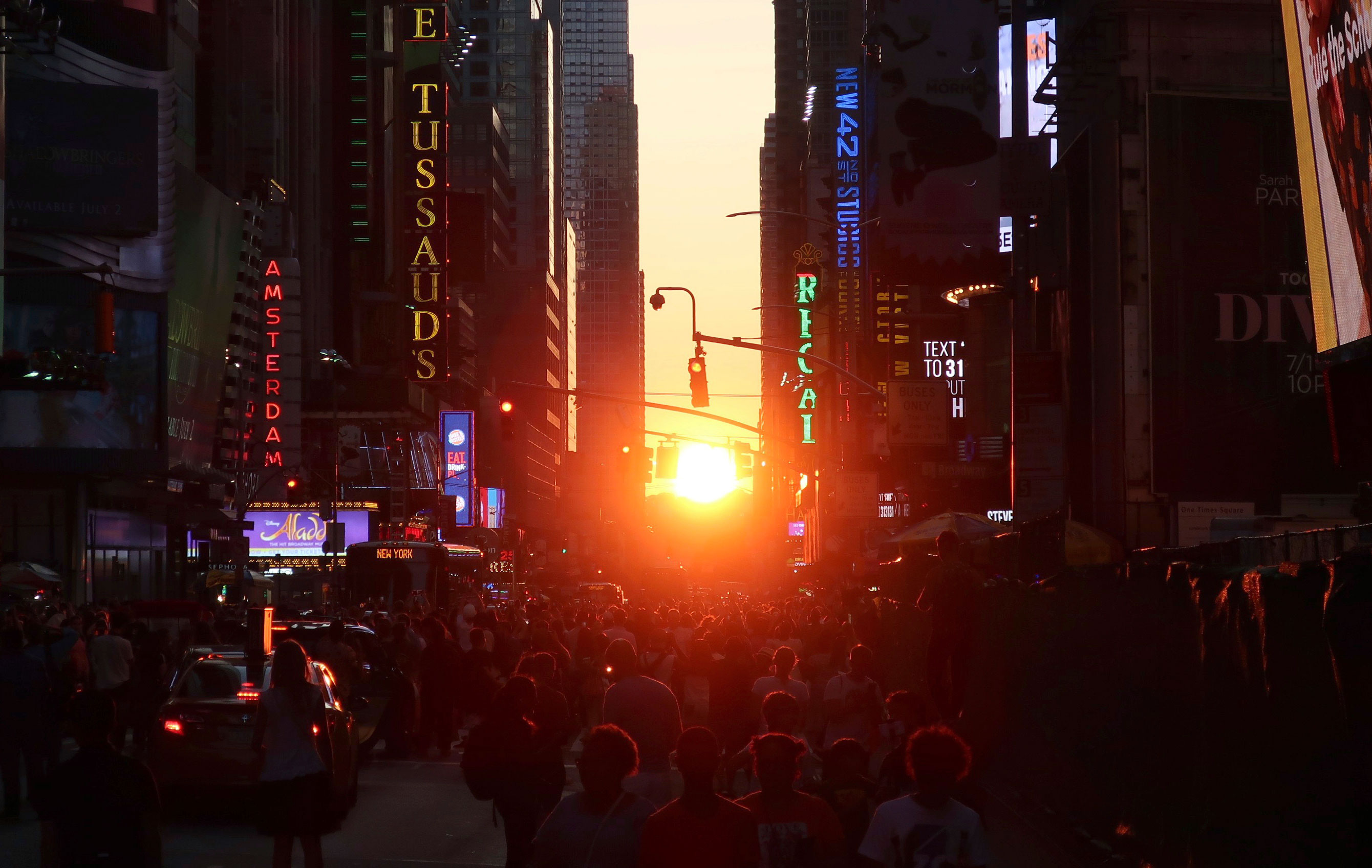 People view a Manhattanhenge sunset on  July 12, 2019, in New York. Manhattanhenge is when the setting sun intersects with the Manhattan street grid. It happens four times a year, but clouds often block the view.