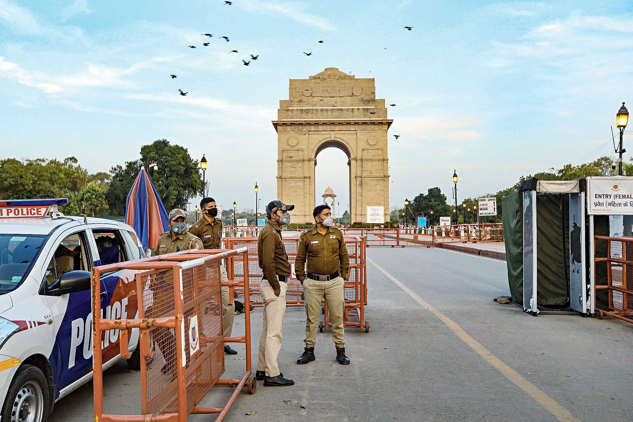 Security personnel wearing masks stand guard at the India Gate in New Delhi on Wednesday.