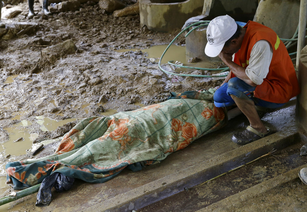 Pio Badangayon cries as she sits next to the body of her son-in-law Edwin Banawol after it was retrieved by rescuers in Itogon in the Benguet province in northern Philippines.