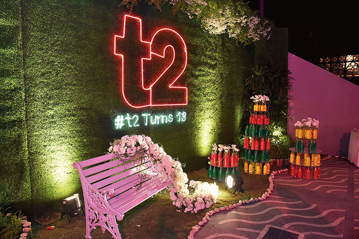 """One of the prettiest and most photographed spots of the night was this green wall with a neon t2 logo that greeted you right as you entered the party area. It was done by Baisakhi Ghosh, conceptualiser and managing director of BFPL. """"This was like an organic and breathable space with greenery and flowers. We had a backdrop with greens with a 4ft t2 written in neon pink with the party hashtag. This space was also done up with around 70 bottles filled with edible psychedelic colours and chrysanthemums on a pretty white bench,"""" said Baisakhi."""