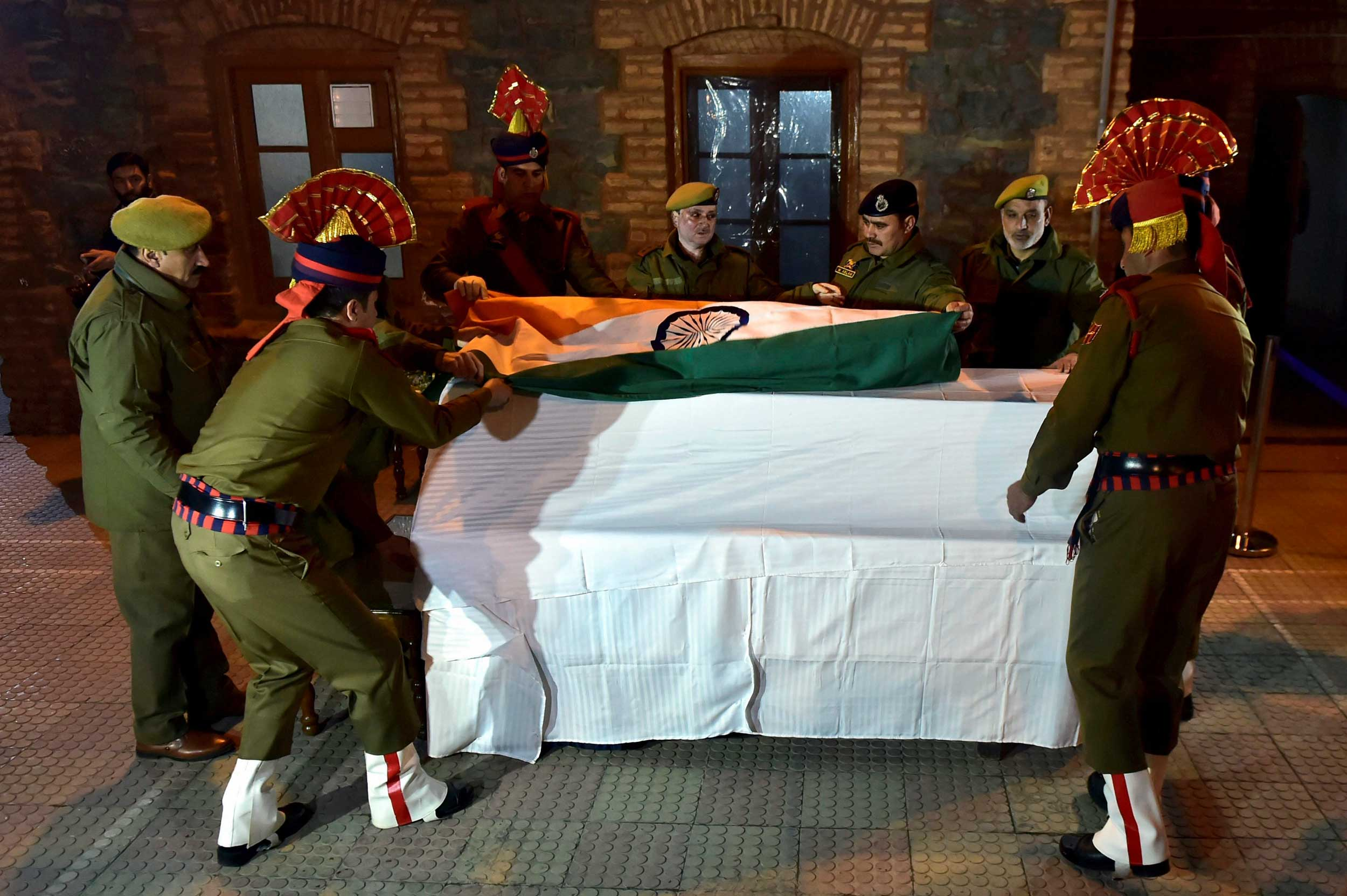 Policemen wrapping the coffin of Aman Kumar Thakur with the Indian Tricolour at the wreath laying ceremony at Trigam Village of Kulgam, in Srinagar, on Sunday.