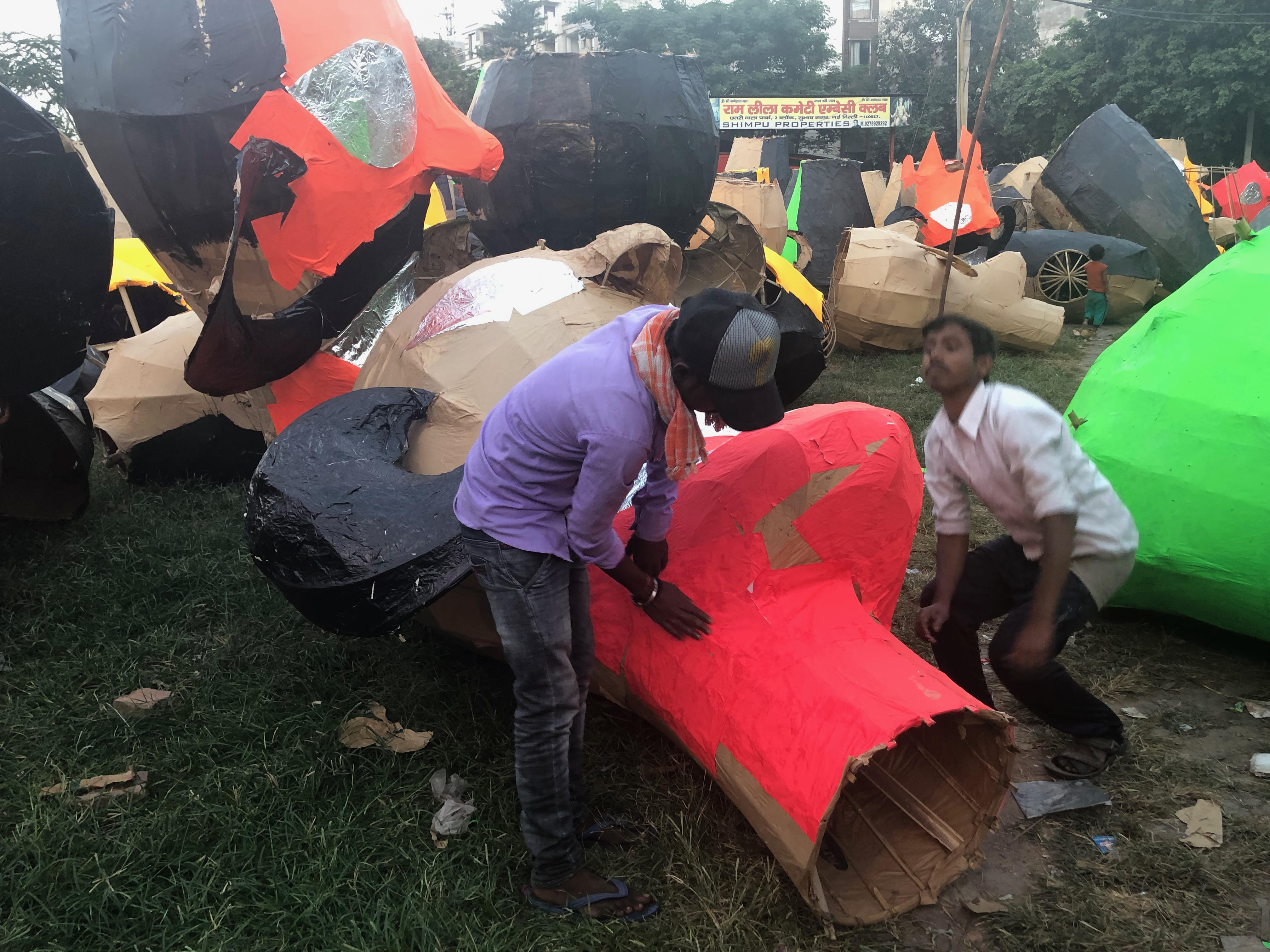 Workers adding colour paper to an effigy