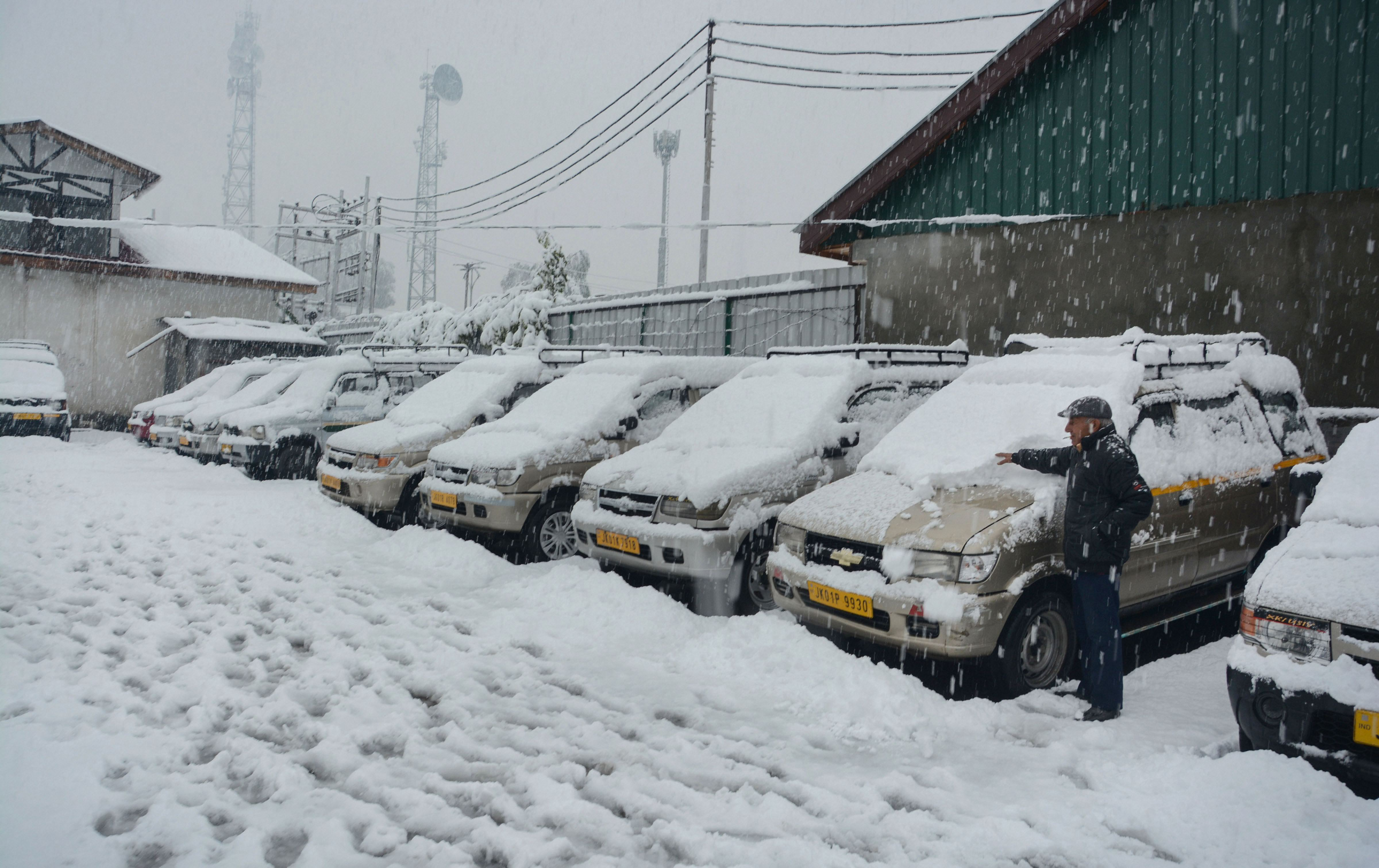A taxi owner removes snow from his vehicle during the season's first heavy snowfall, in Srinagar, Thursday, November 7, 2019.