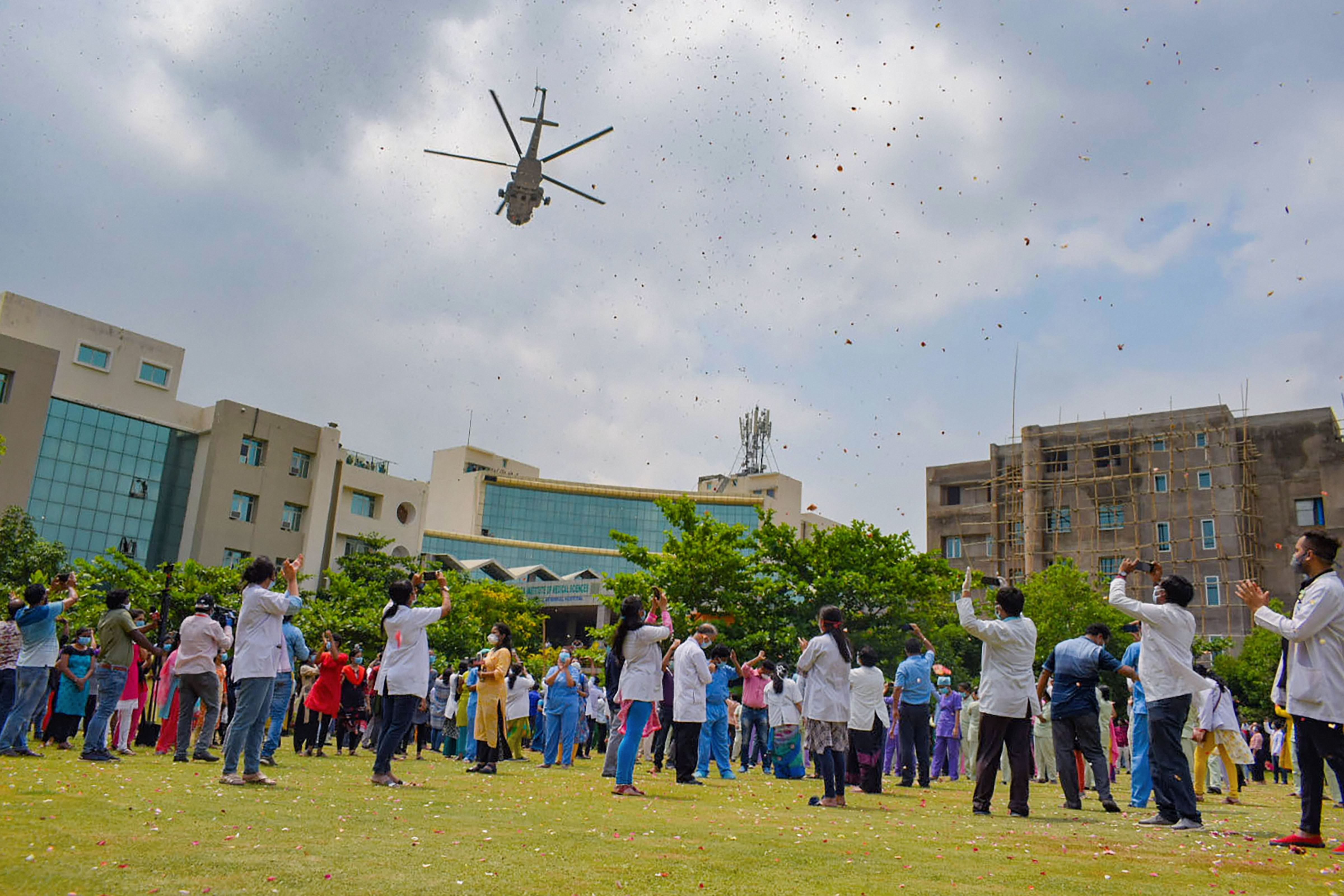 An Indian Air Force chopper showers flowers on medical professional at Kalinga Institute of Medical Science to express gratitude towards them in fighting Covid-19, in Bhubaneswar, Sunday, May 3, 2020.