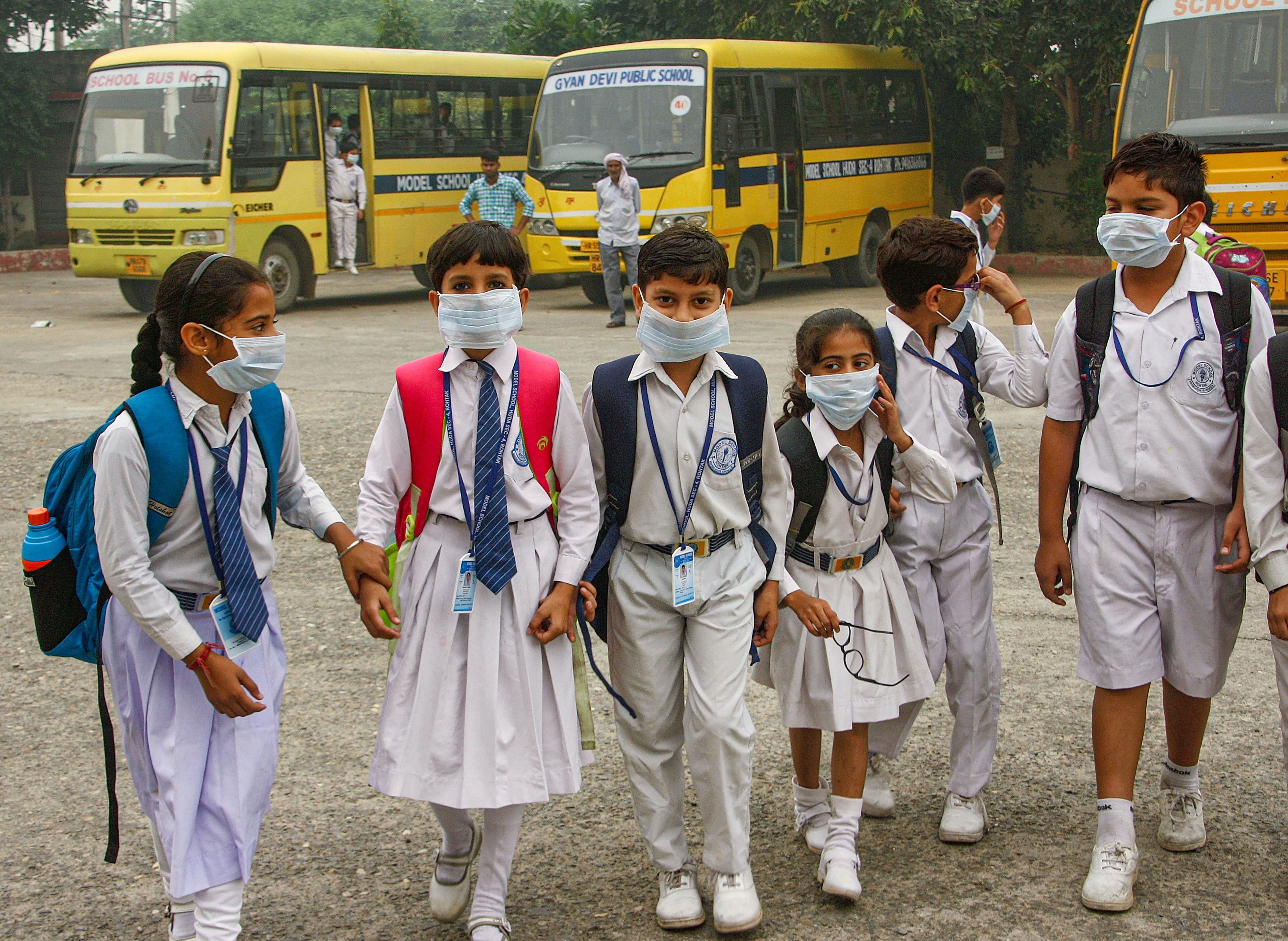 Students wearing mask walk amid an atmoshphere shrouded in smog in Rohtak, Saturday, November 2, 2019.