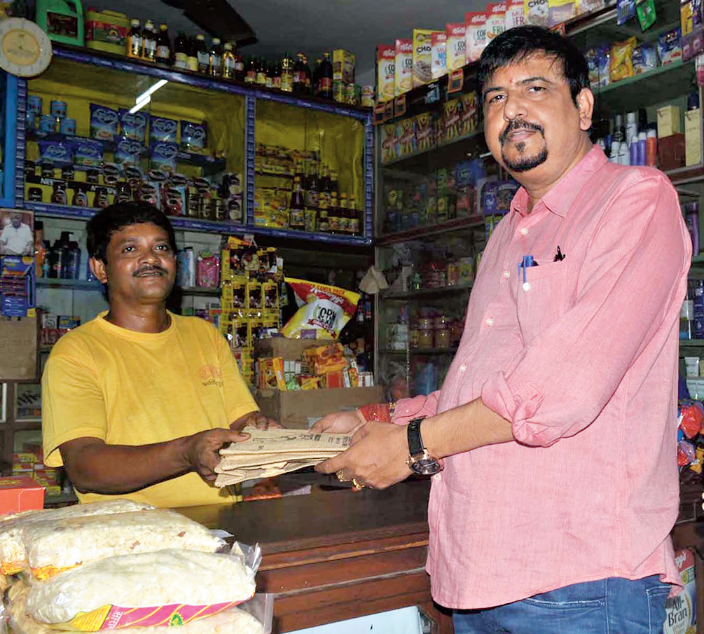 MLA Sujit Bose hands over jute bags to a shopkeeper in CA Market after the event on Sunday. The corporation plans to impose fines on shopkeepers for plastic use after the Pujas.