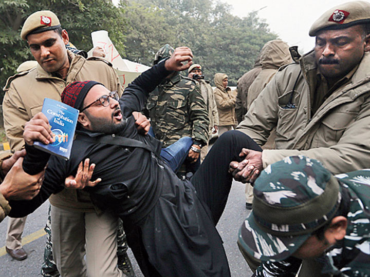 Policemen detain a protesting student, holding a book on the Indian Constitution, outside Uttar Pradesh Bhawan in New Delhi, on December 27, 2019.
