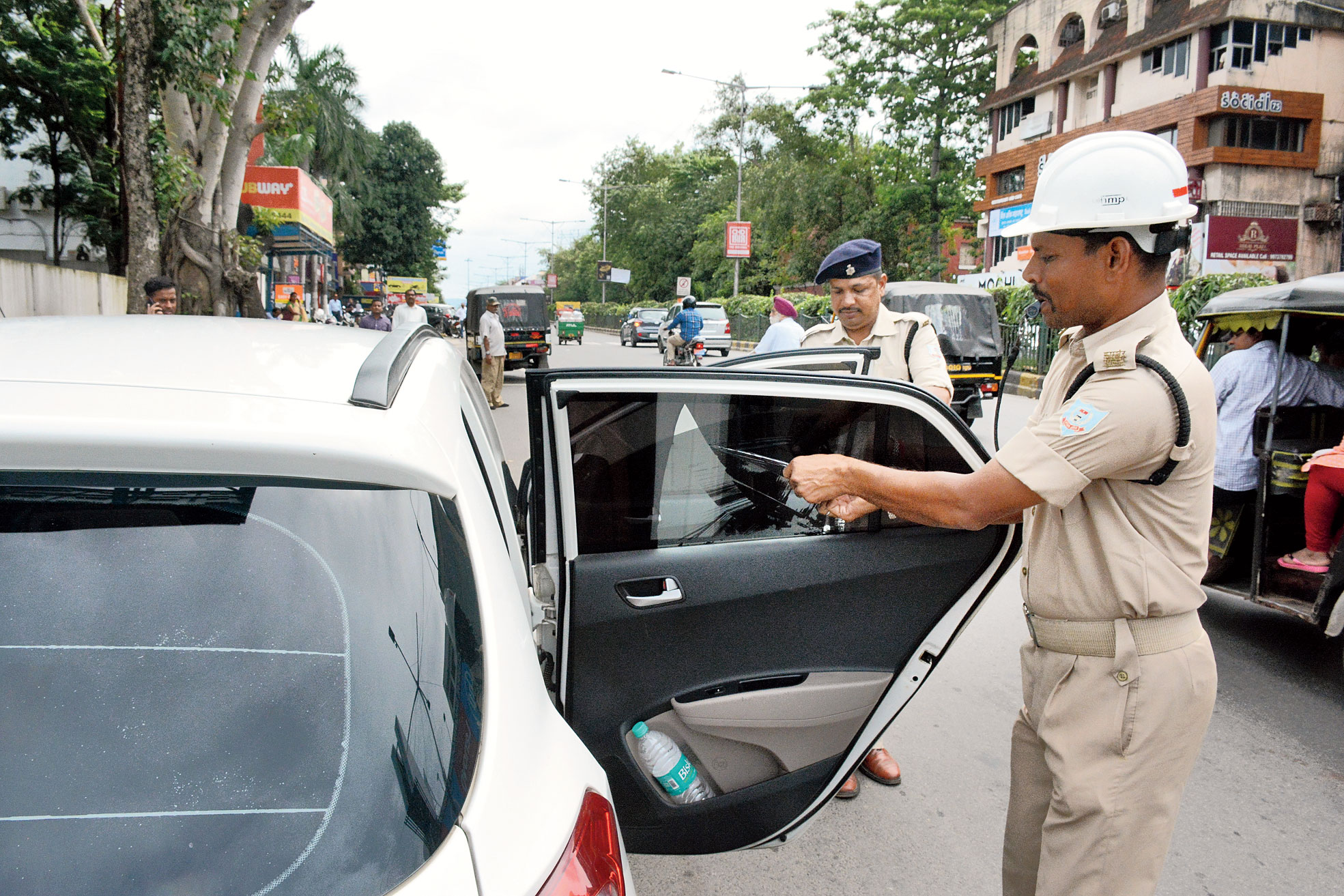 A traffic cop peels off tinted film from a car in Bistupur, Jamshedpur, on Tuesday.