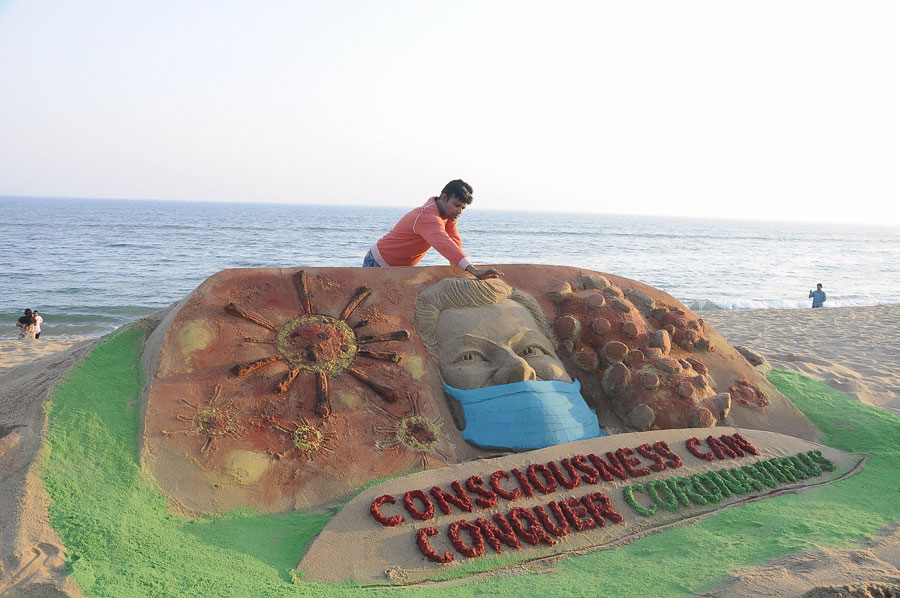 Sand artist Manas Sahoo makes a sand sculpture to create awareness against coronavirus, at Puri, Odisha