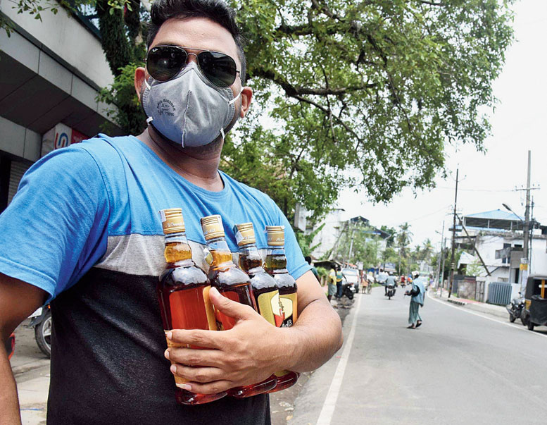 A man leaves after buying liquor from a shop in Kochi on May 28.
