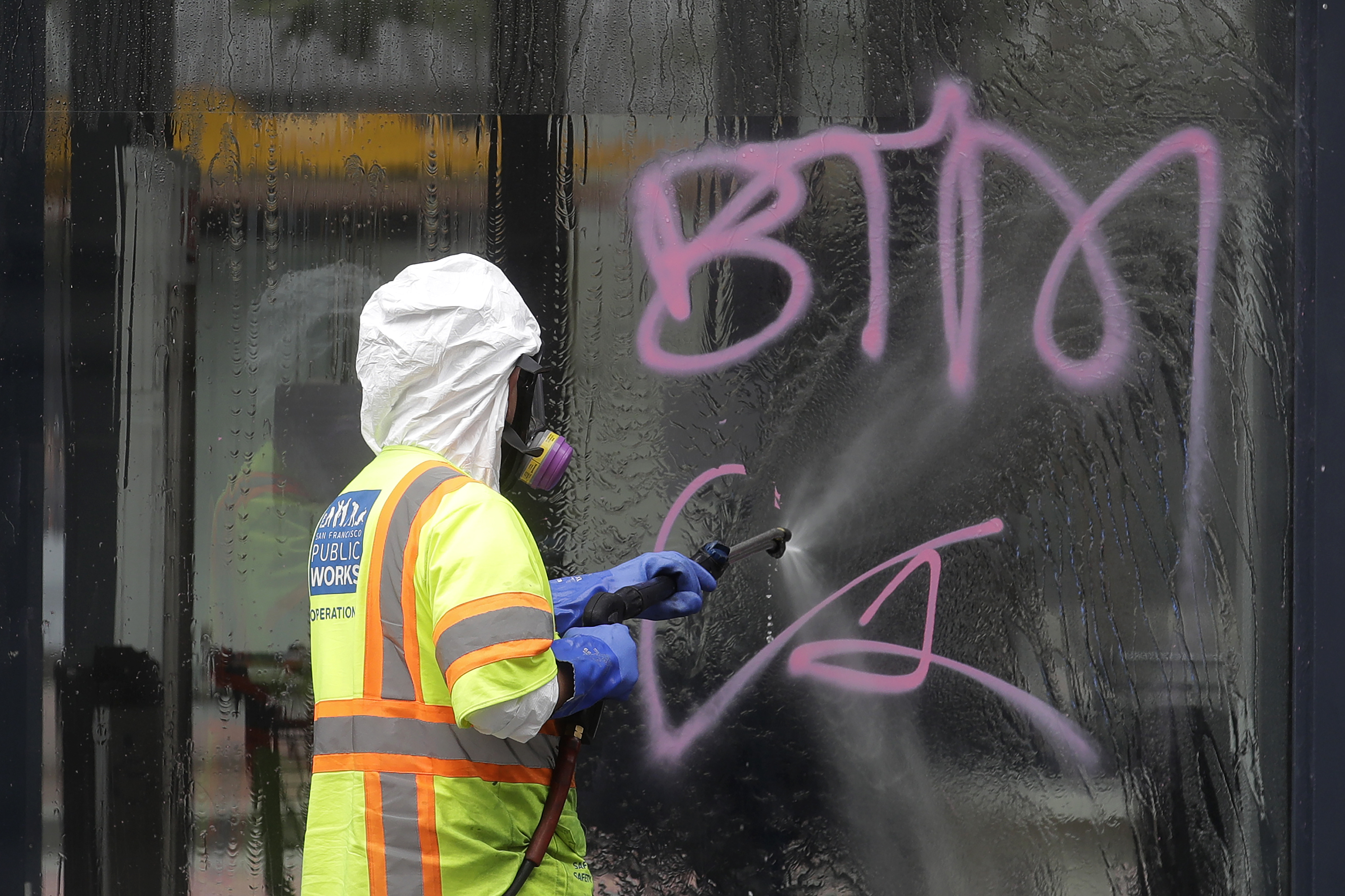 A worker with San Francisco Public Works cleans graffitti off the window of a Marshalls store in San Francisco