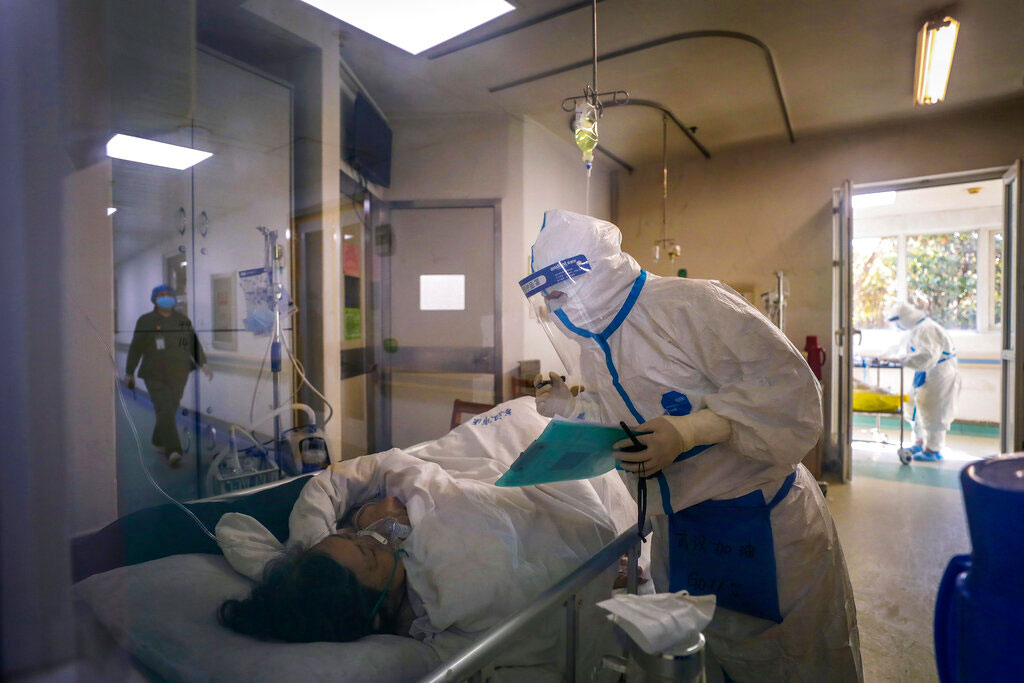 A medical worker checks on a patient's condition at Jinyintan Hospital in Wuhan, China.