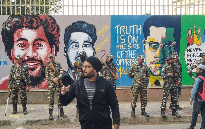 Security personnel stand guard in front of a wall painted with anti-CAA murals, outside Jamia Milia Islamia University in New Delhi, on Tuesday