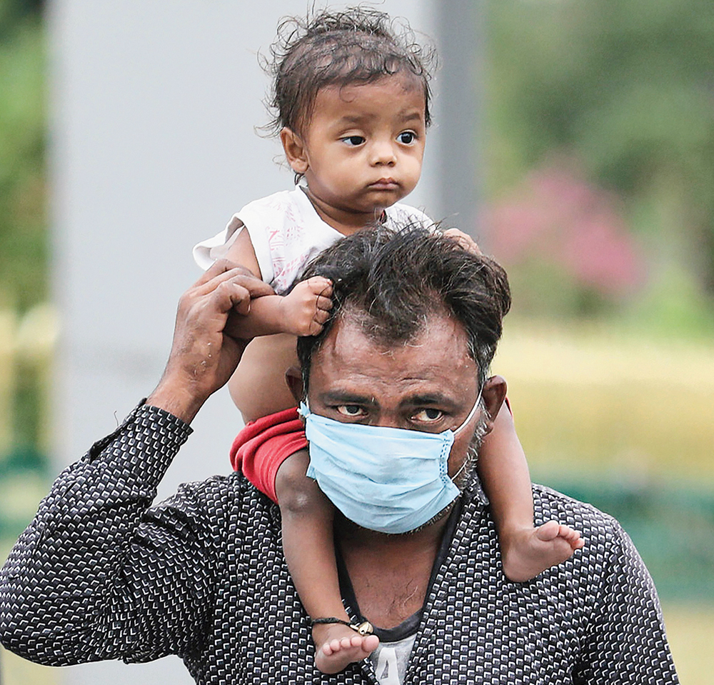 A passenger carrying his child arrives at Jammu railway station to board a special train to New Delhi on Saturday. The misery of travellers has become a testimony to the humanitarian crisis triggered by the abrupt lockdown that stretched for over two months and its haphazard implementation.