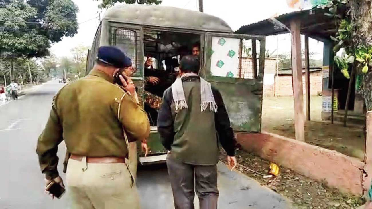 Teacher Sudipta Singha being taken to a police van after being rescued from the agitators in Daribhit on Saturday.