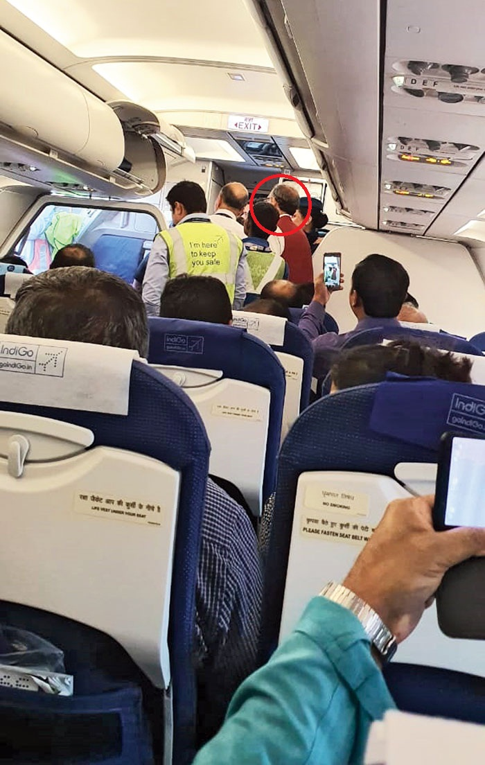 Co-passengers try to capture a picture of Abhijit (circled) as he is about to get off the flight