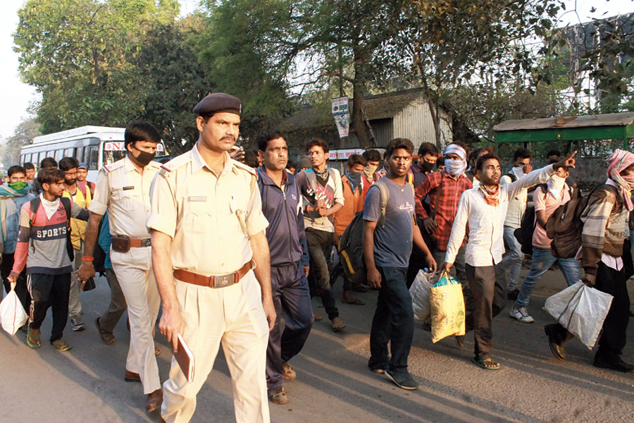 Cops escort passengers to special buses in Jamshedpur on Monday.