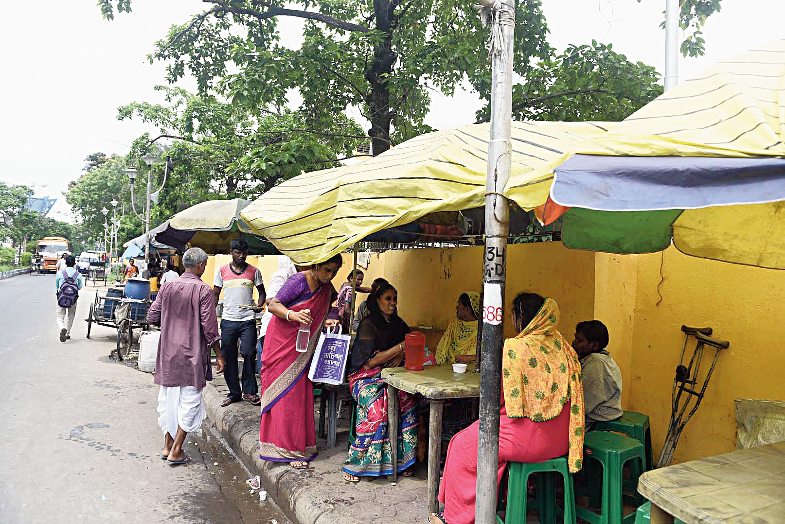 Customers at a food stall on the footpath outside the National Institute of Homoeopathy in Salt Lake on Thursday.