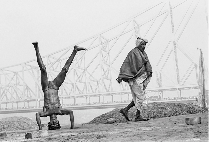 """An early morning shot of two men. """"While the young  man is standing on his head, the older one is on his feet. I found  the contrast interesting,"""" says the photographer."""