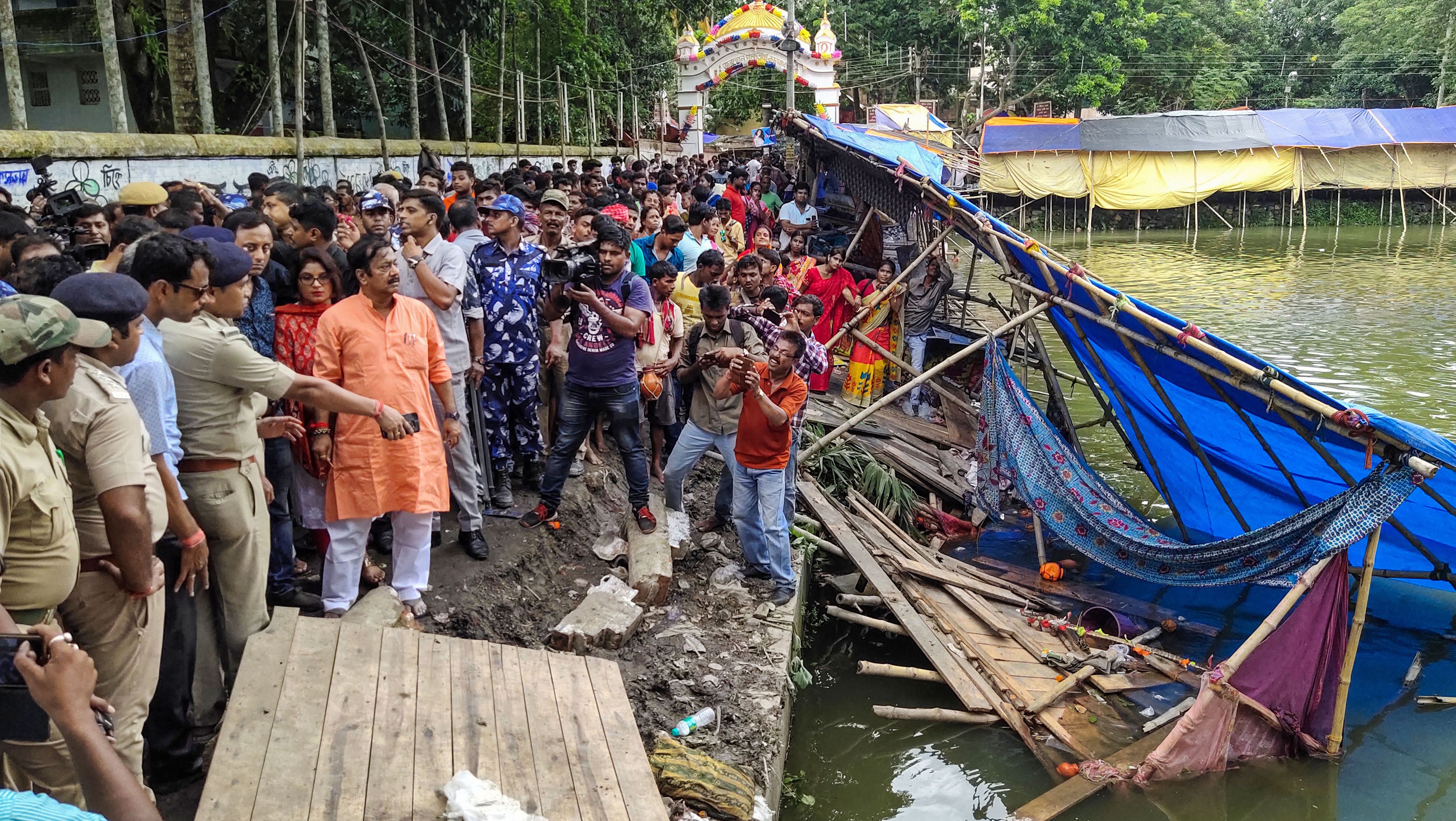 Police personnel investigate the site where a wall collapse in Kachua triggered a stampede like situation, in North 24 Parganas district of West Bengal, Friday, August 23, 2019.
