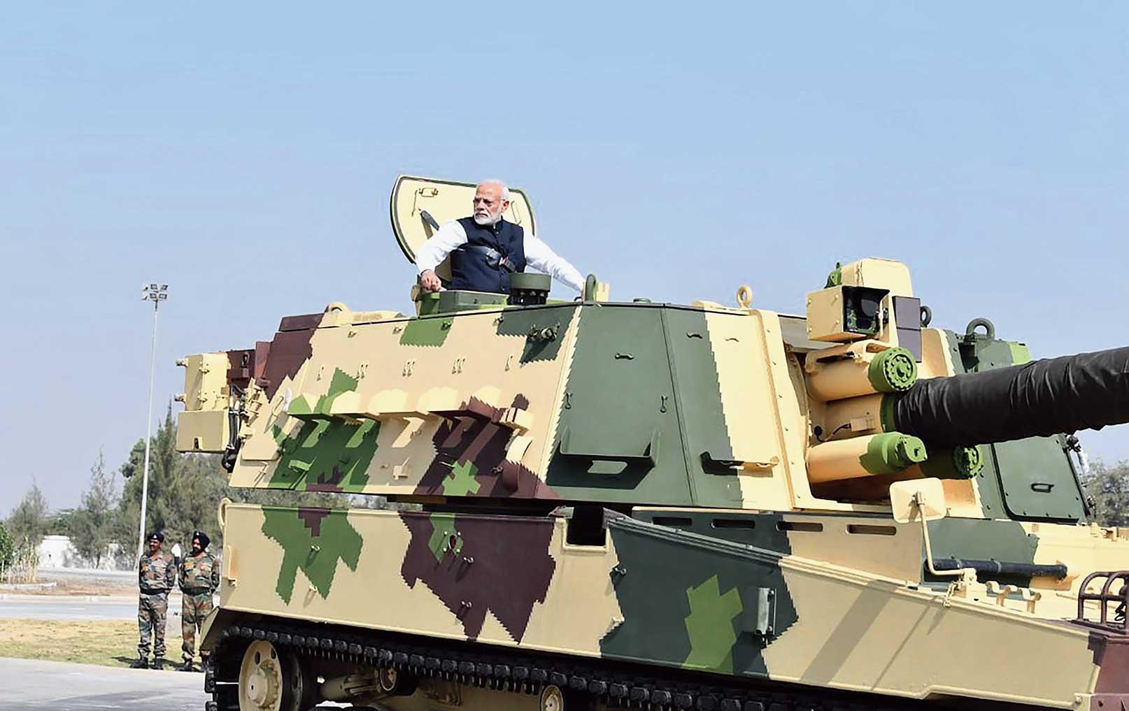 Military Modi: Modi rides a K-9 Vajra self propelled howitzer built by Larsen & Toubro in Hazira, Gujarat, on Saturday.