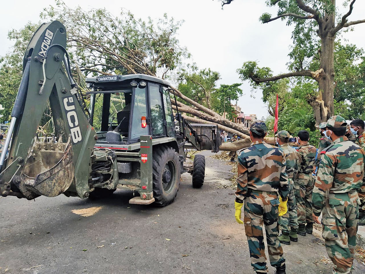Army jawans stand by as one of their colleagues operates a JCB to clear a fallen tree in Salt Lake