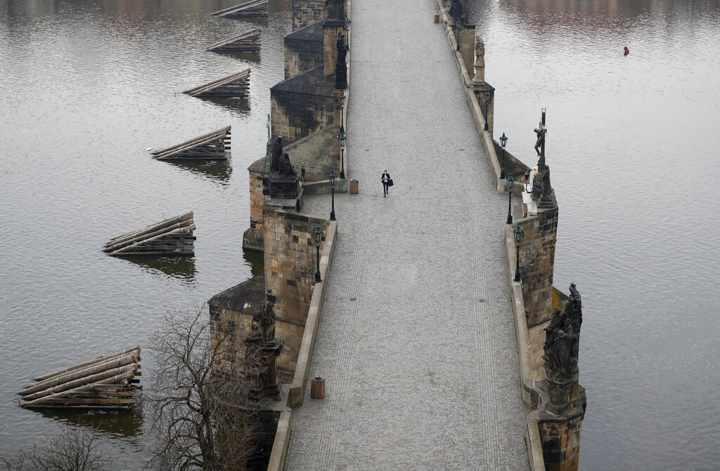 A woman walks across the near empty Charles Bridge in Prague, Czech Republic, Friday, March 20, 2020. The Czech Republic's government has approved further dramatic measures to try and stem the spread of the novel coronavirus called COVID-19. The Prague castle is in the background.