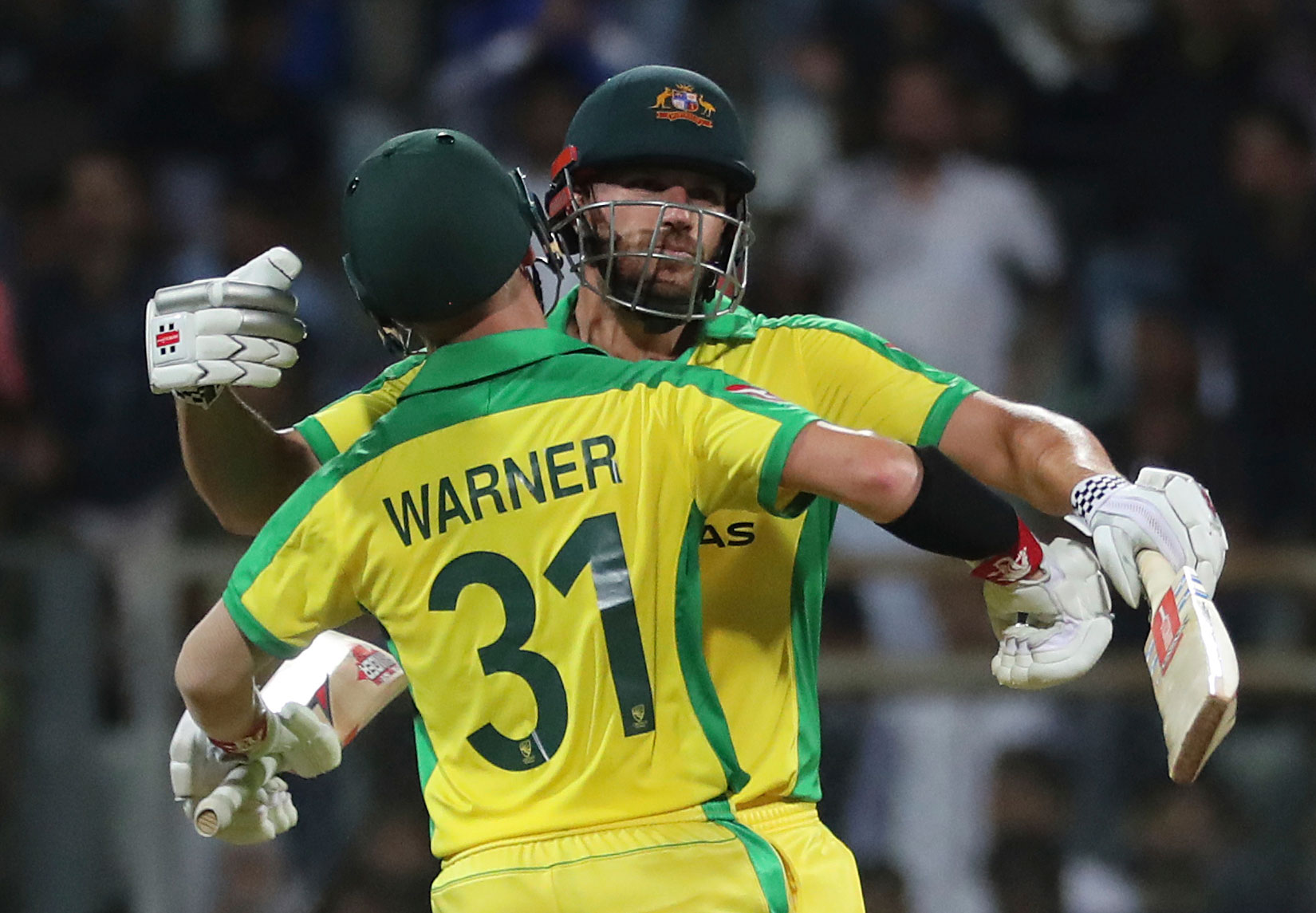 Australia's captain Aaron Finch greets David Warner after they won the match against India during the first one-day international cricket match between India and Australia in Mumbai, India on Tuesday