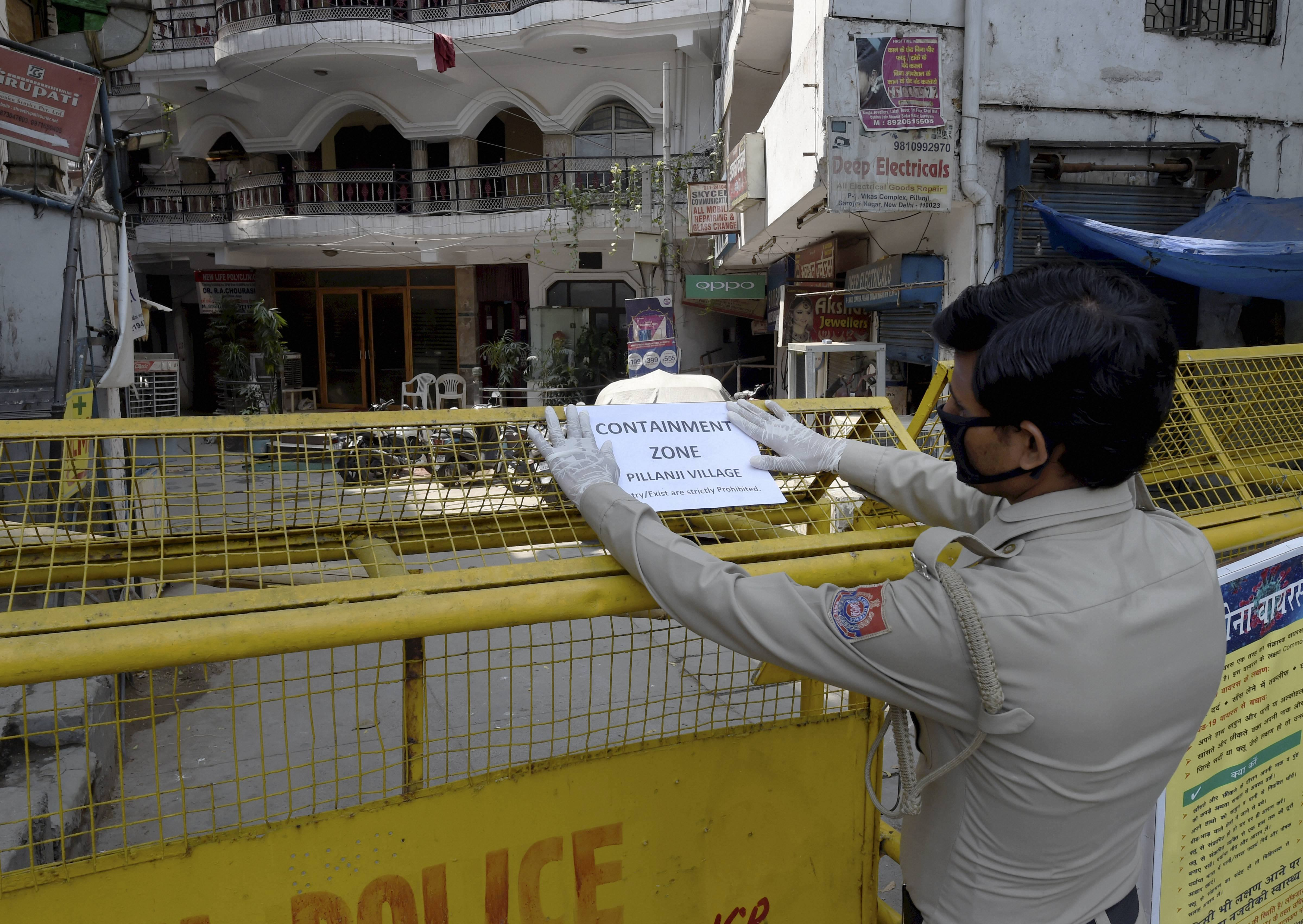 A security guard pastes a notice on a barricade at Pilanji village area, identified as a Covid-19 containment zone, in New Delhi on Tuesday.