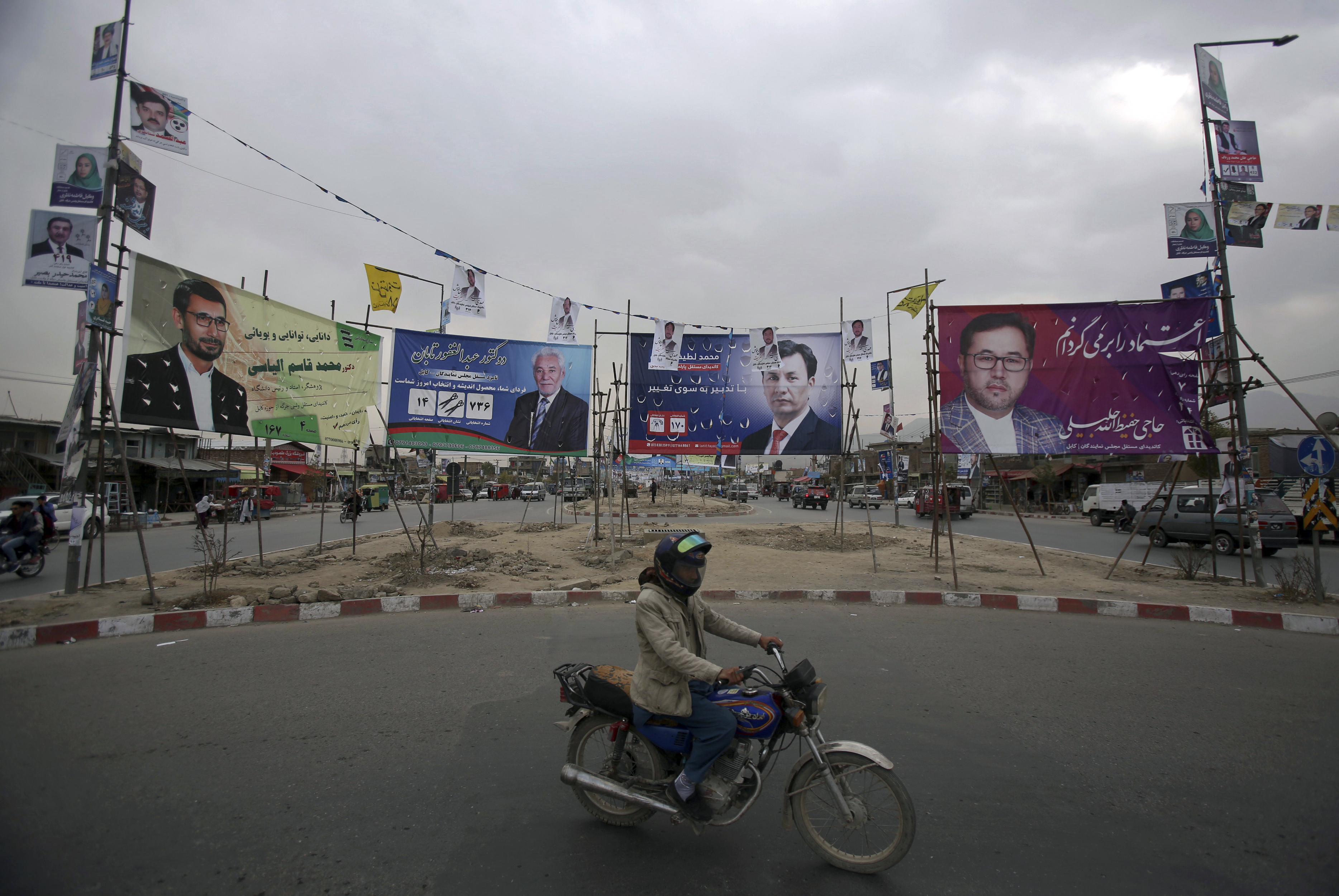 A man rides his motorbike in front of campaign posters for parliamentary candidates in Kabul. Afghans will return to the polls on Saturday, hoping to bring change to a corrupt government that has lost nearly half the country to the Taliban.