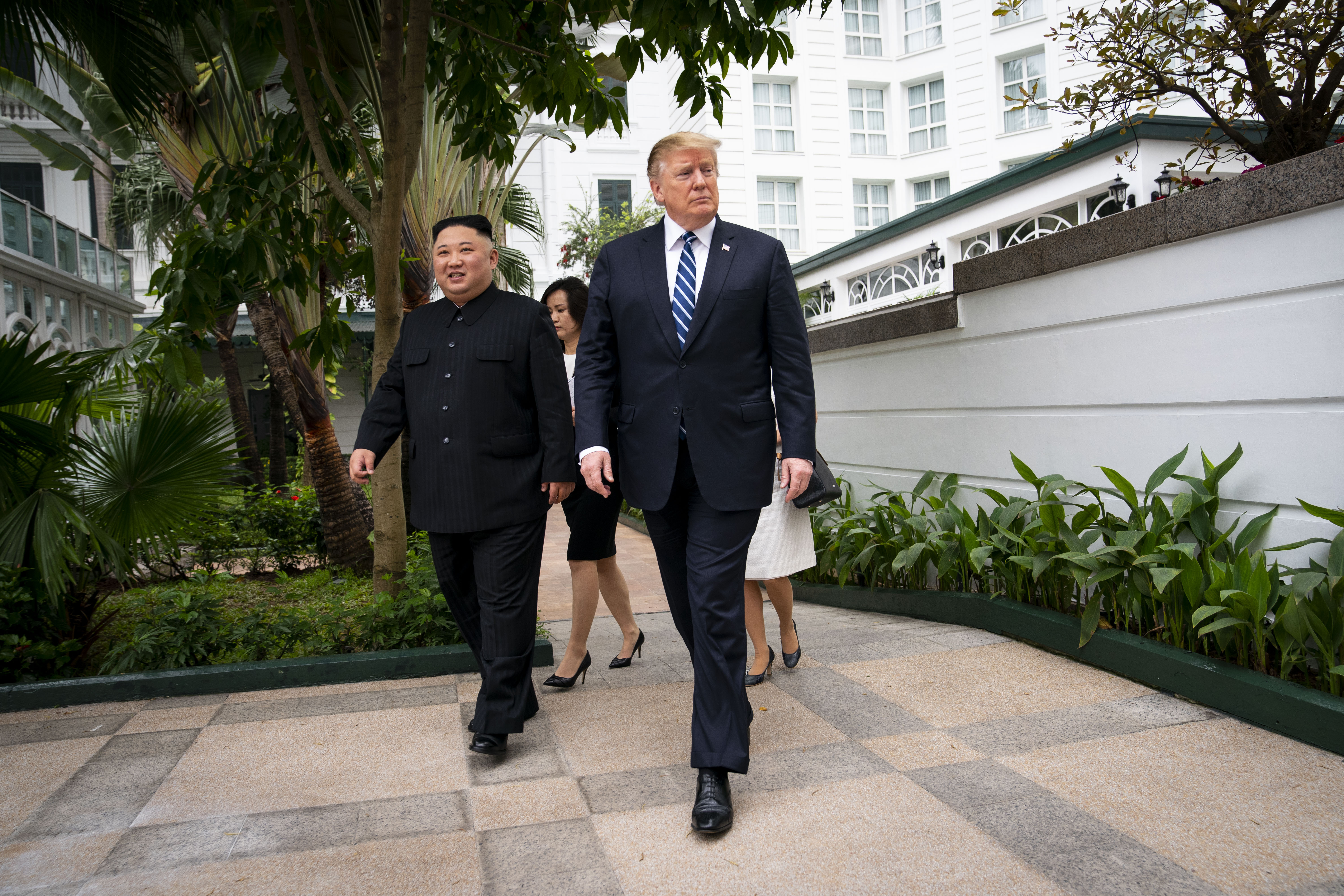 Donald Trump and Kim Jong-un walk together to the meeting at the Metropole Hotel in Hanoi on Thursday.