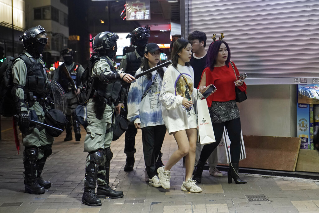 Police guide tourists across the road as they prepare for action against protesters during a rally on Christmas Eve in Hong Kong, Tuesday, Dec. 24, 2019. More than six months of protests have beset the city with frequent confrontations between protesters.